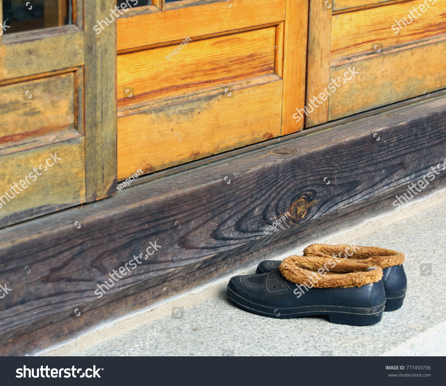 667f2d2d5a9591 pair of fur lined rubber winter shoes outside wooden doors of Buddhist  temple retreat South Korea