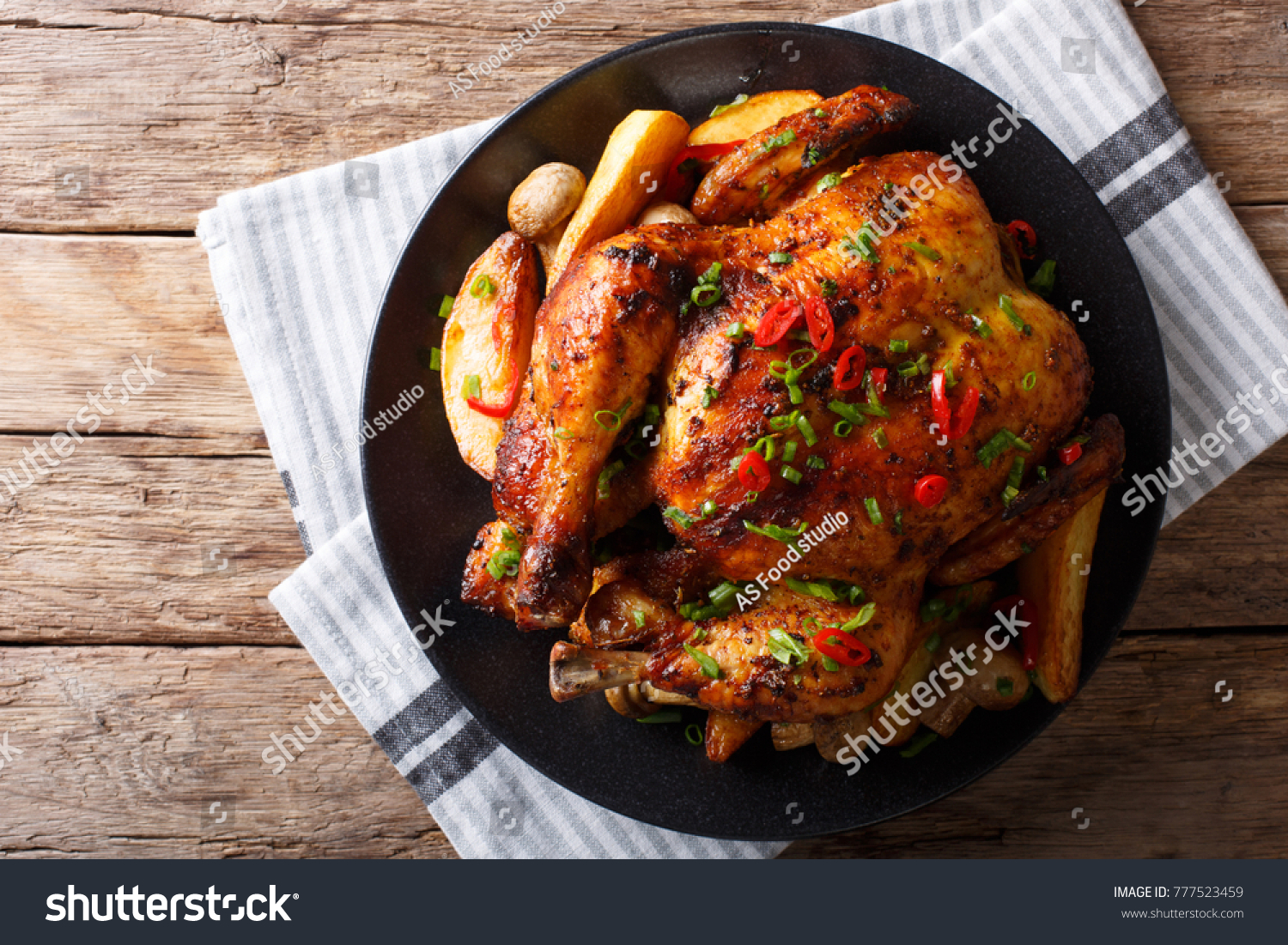 Baked whole chicken with mushrooms and potatoes close-up on a plate on a table. Horizontal top view from above #777523459