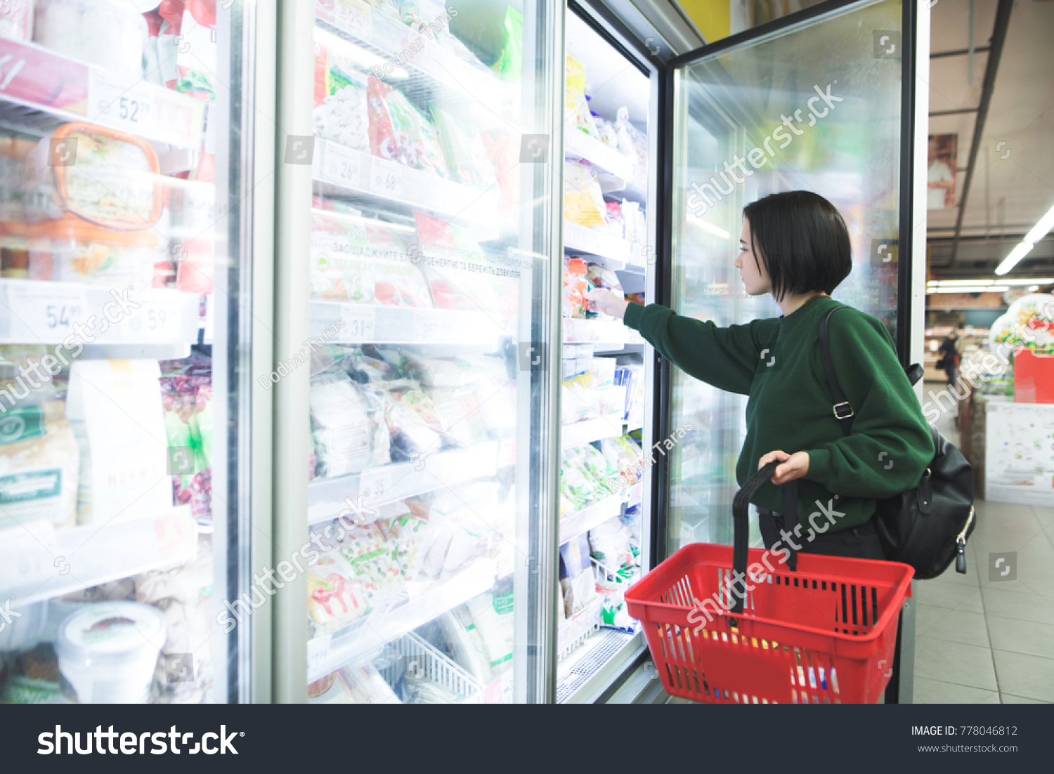 A girl with a basket takes frozen foods from the supermarket's refrigerator. The girl chooses goods in the store. Shopping in the supermarket. #778046812