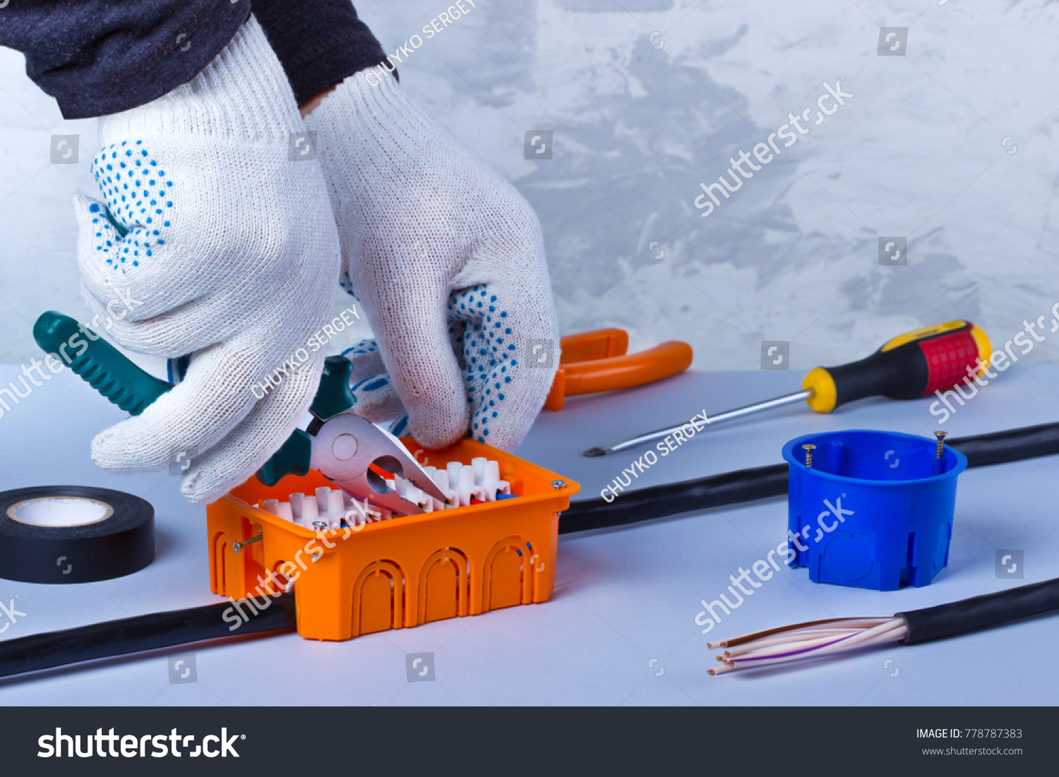 Hands of electrician with pliers repair equipment in fuse box