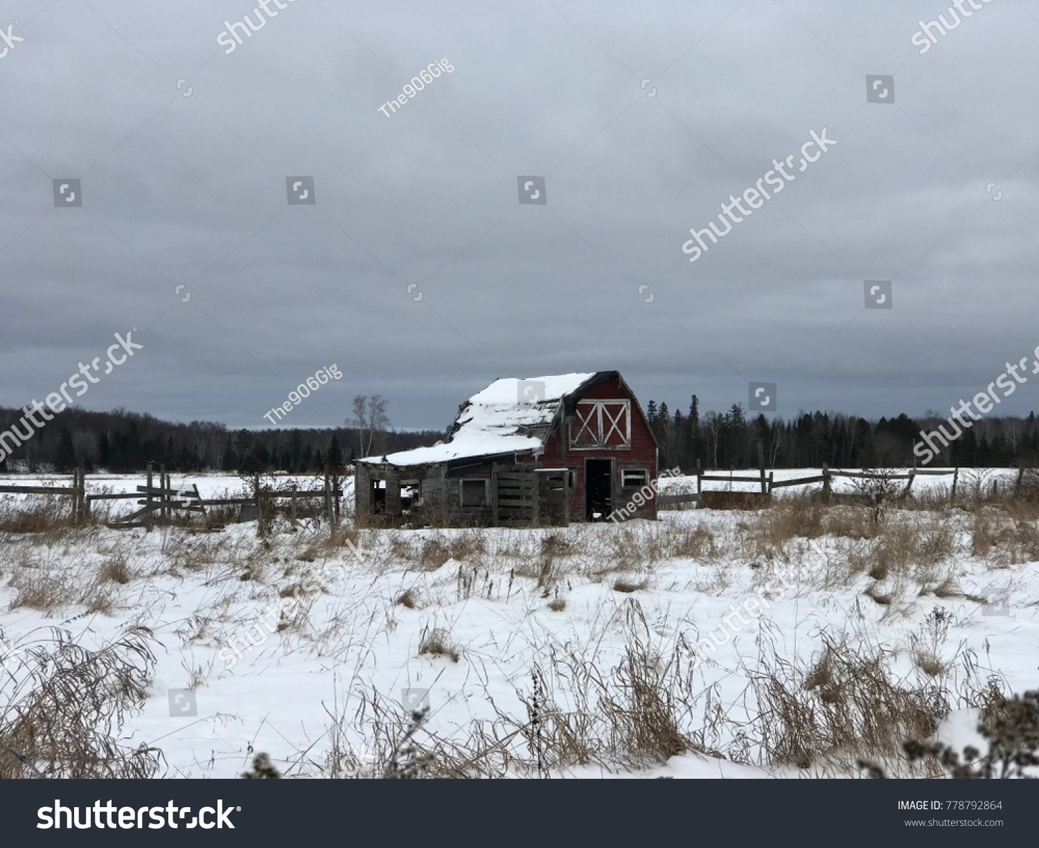 Abandoned barn with fence and barbed wire on a snowy winter ...
