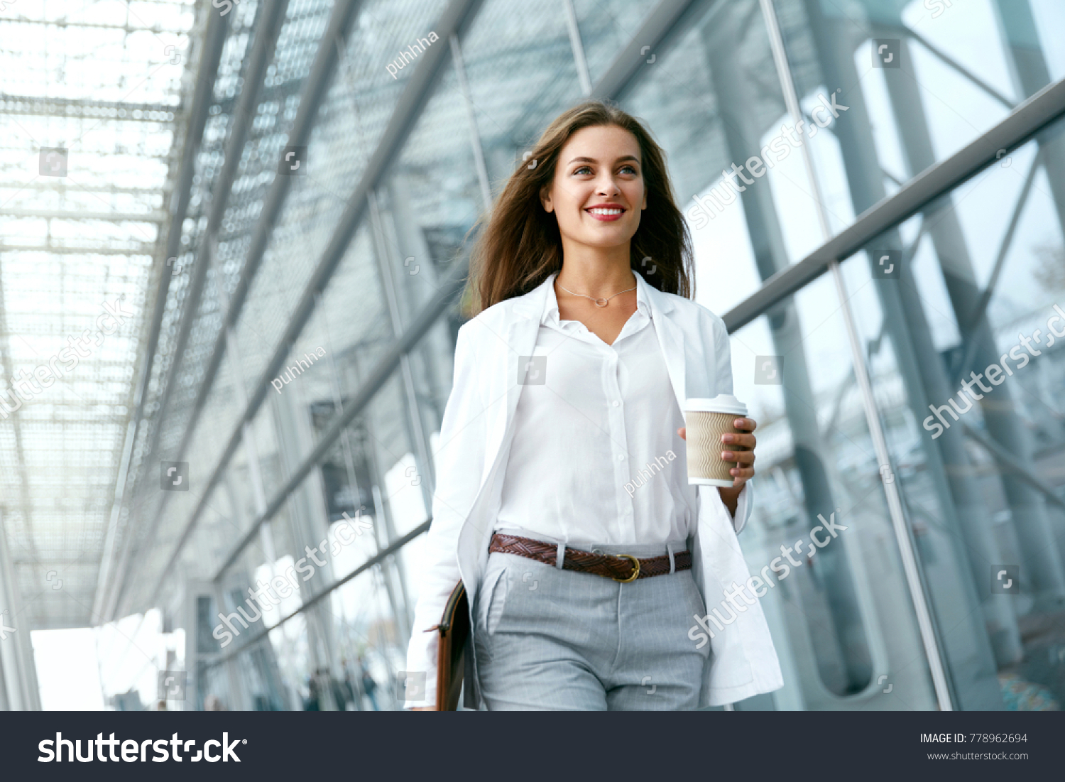 Beautiful Woman Going To Work With Coffee Walking Near Office Building. Portrait Of Successful Business Woman Holding Cup Of Hot Drink In Hand On Her Way To Work On City Street. High Resolution. #778962694