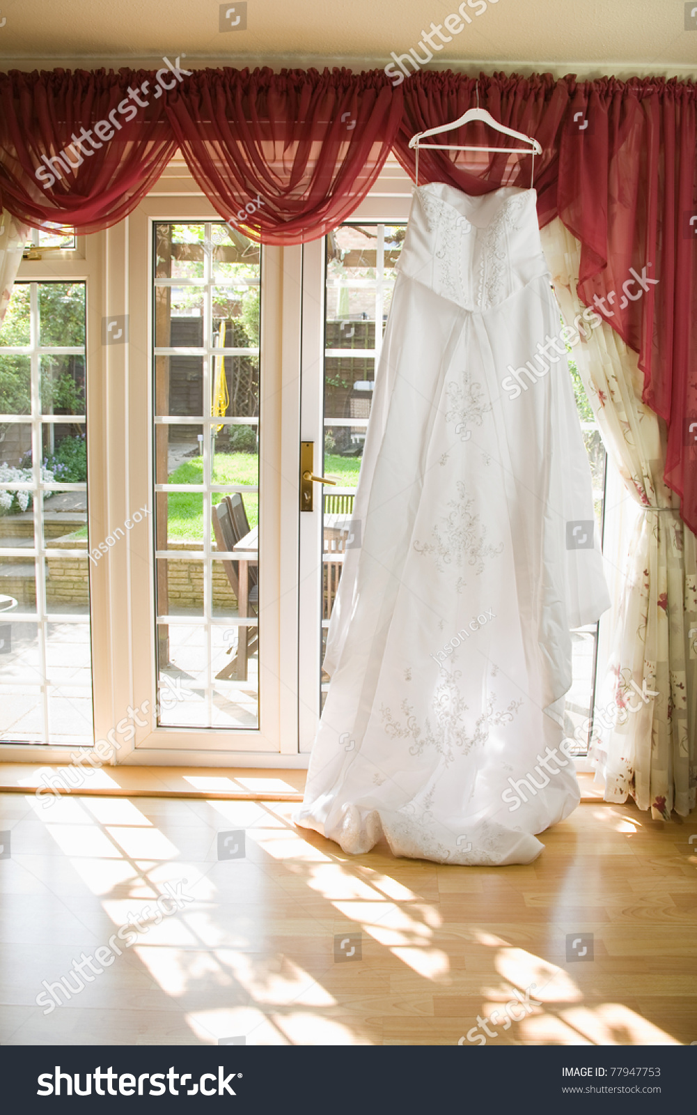 See sun shining through dress - White Wedding Dress Hanging From A Curtain Pole With The Sun Shining Through The Window