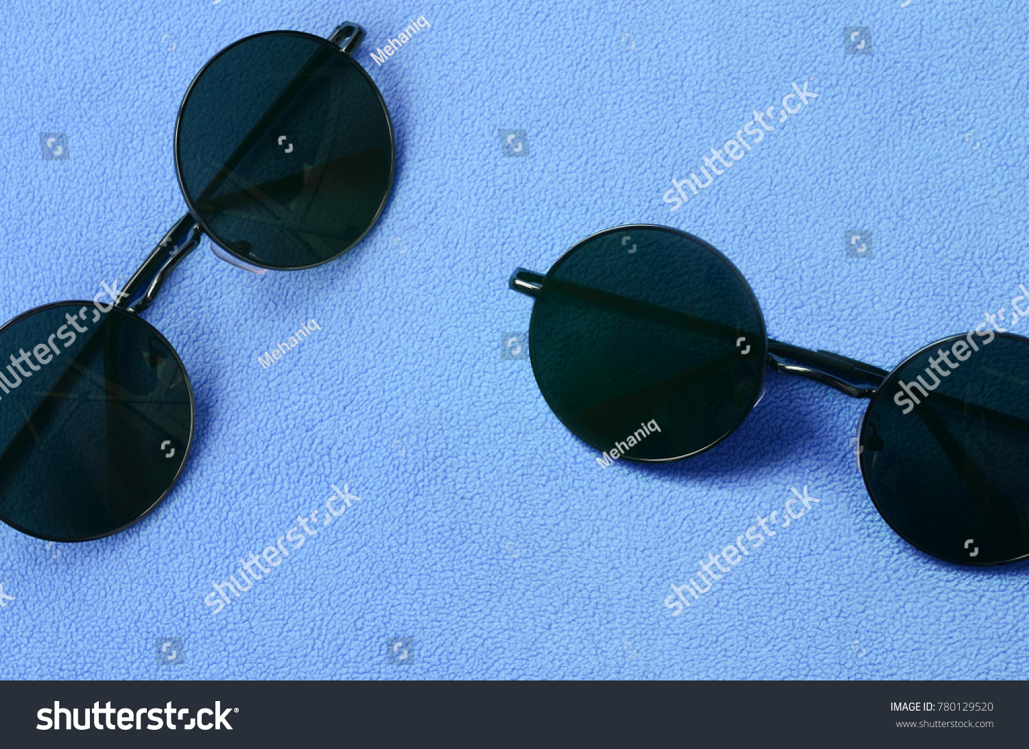 5fe11ad05d28 Two stylish black sunglasses with round glasses lies on a blanket made of  soft and fluffy