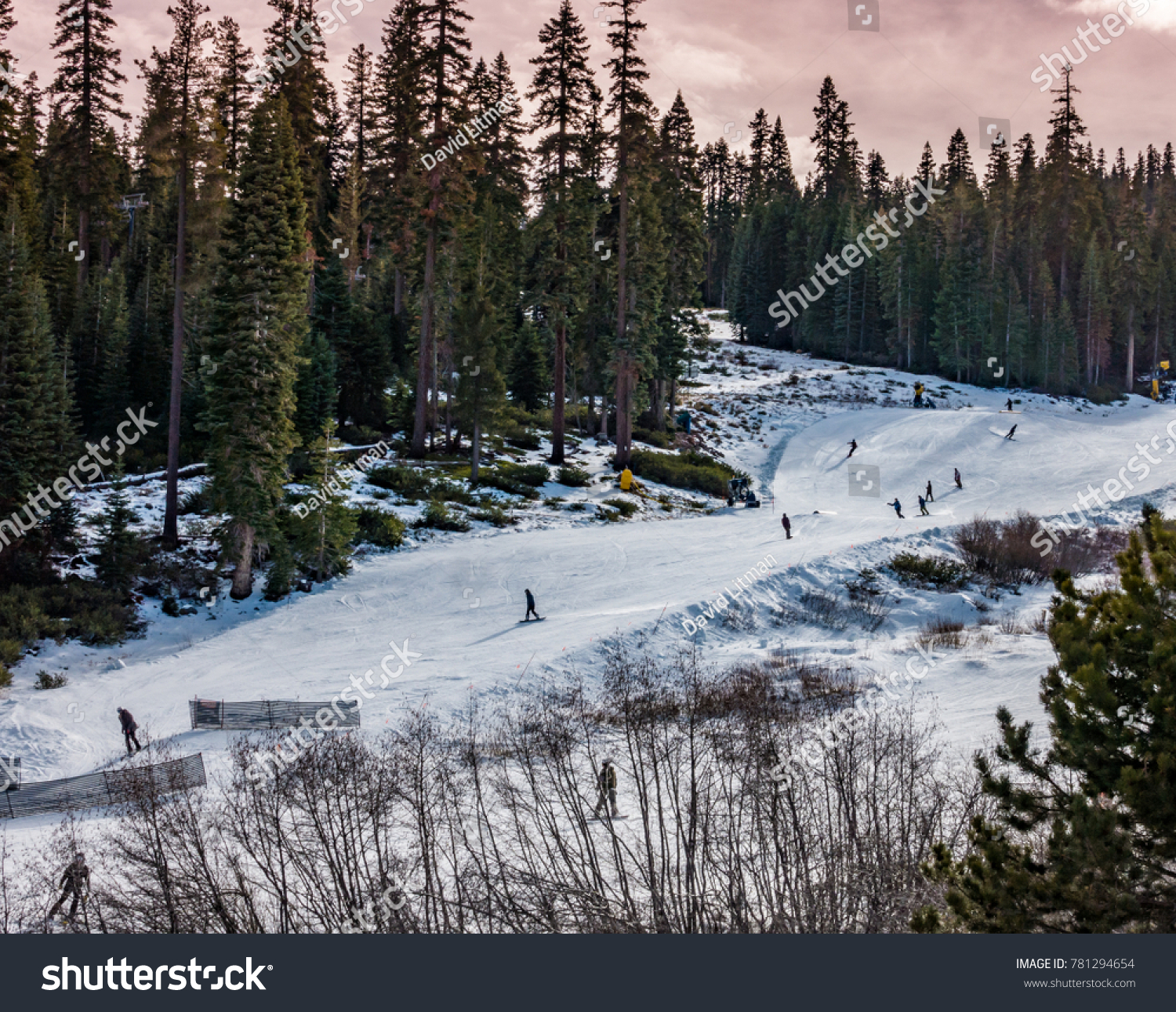 The slopes of Northstar Ski Resort, in the Sierra Nevada Mountains of Truckee California, near Lake Tahoe, with skiers (and snowboarders) skiing the ski runs in the late afternoon, before sunset