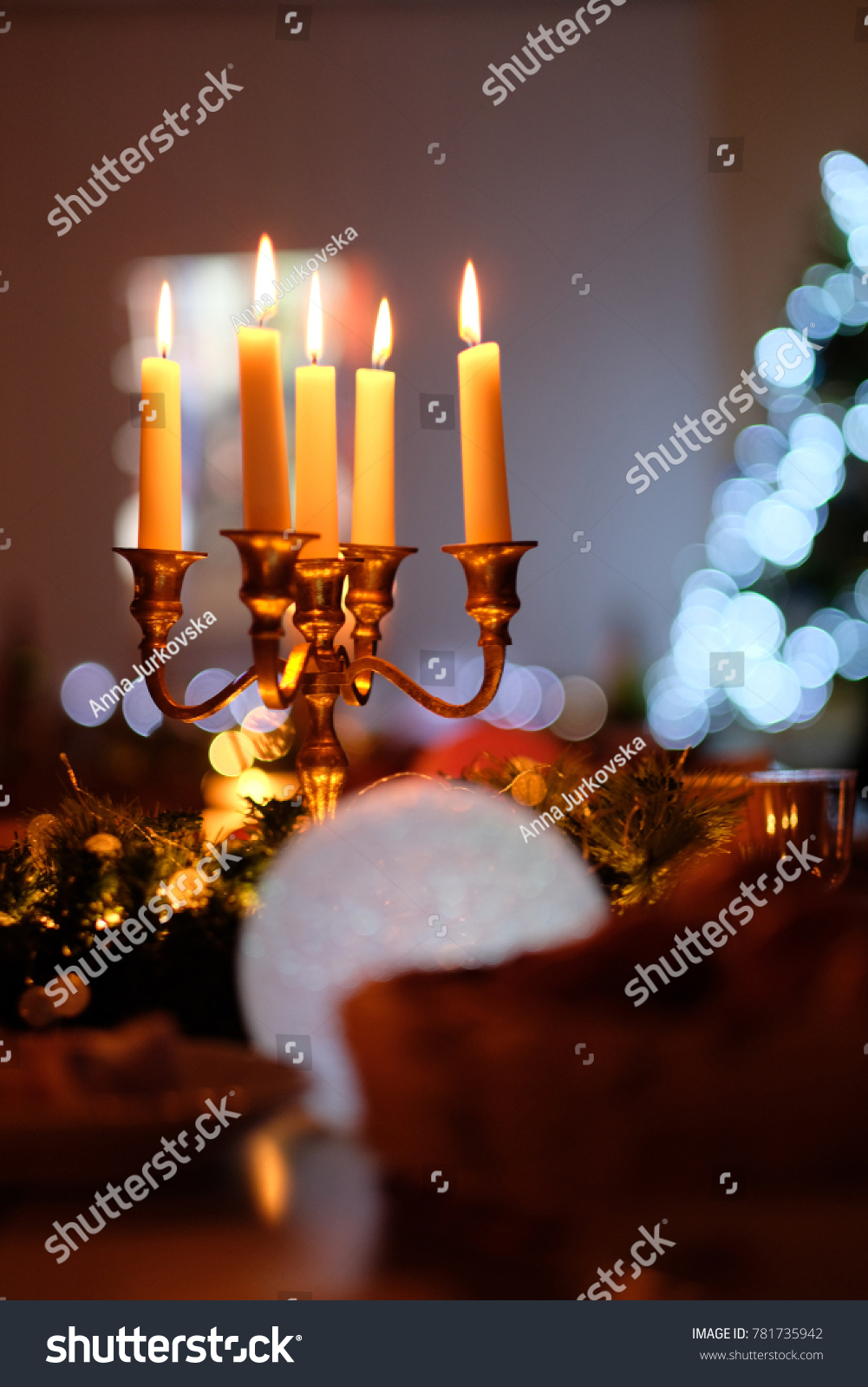 five burning candles in a candelabra among the christmas decor and lights