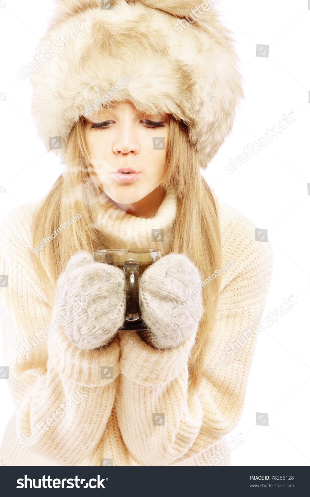 e6d0380444a8 Beautiful young woman in fur cap and sweater blows on hot tea ...