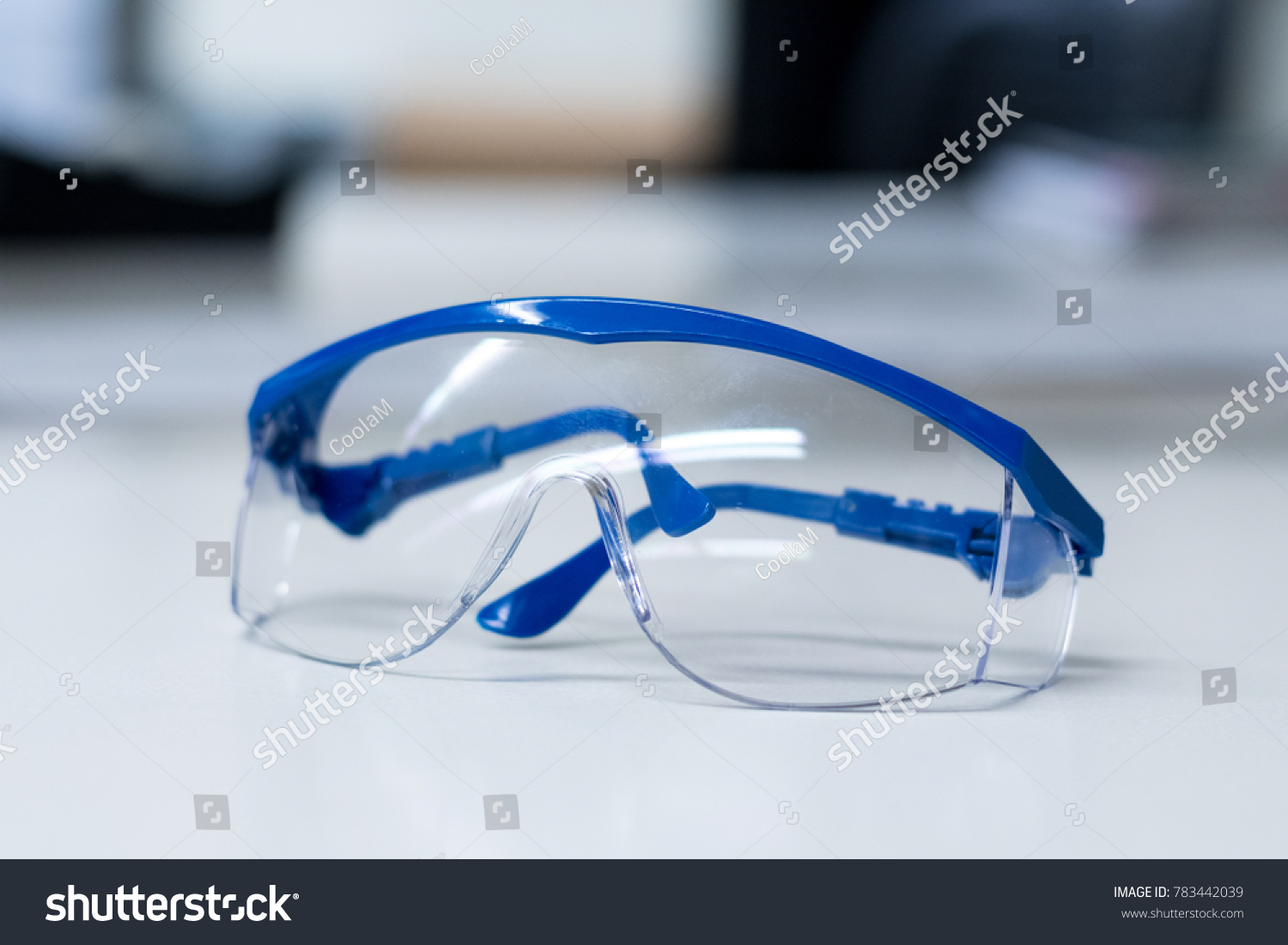 Close-up of blue safety goggles on a desk in a research lab. #783442039
