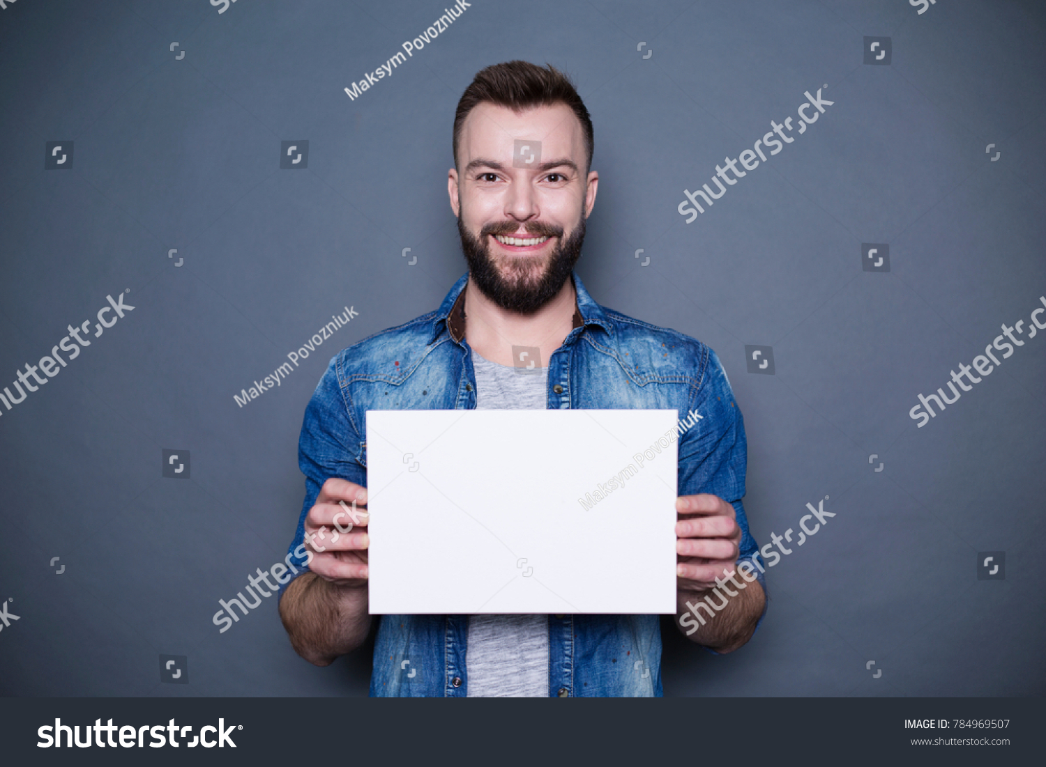 Everything is for you. Handsome young smiling man in a denim shirt shows a white sheet of paper in the camera on a gray background. Area for advertising. #784969507