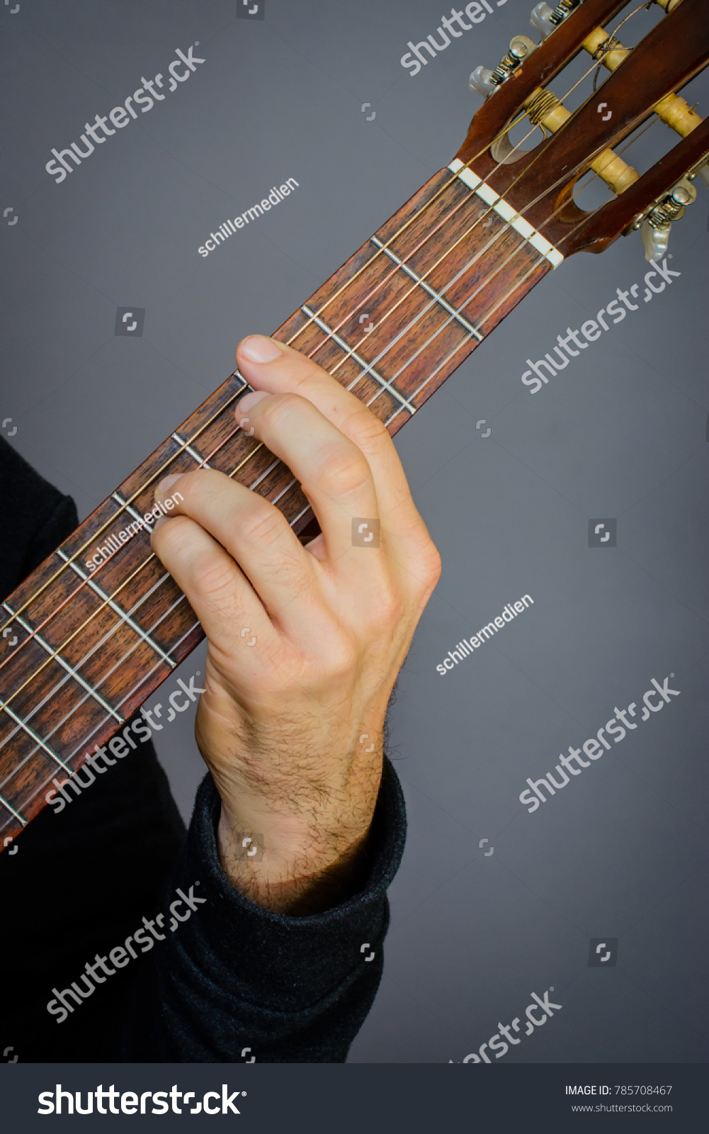 Guitarist Playing An G Minor Chord On Classical Acoustic Guitar With
