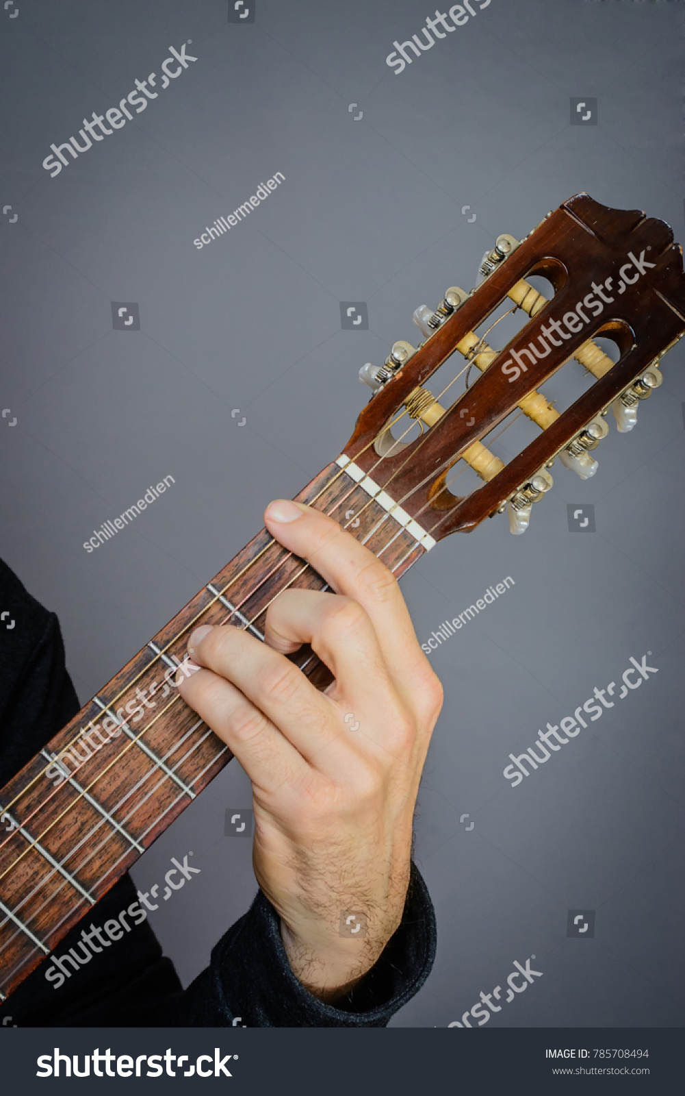 Guitarist Playing An F Major Open Chord On Classical Acoustic Guitar