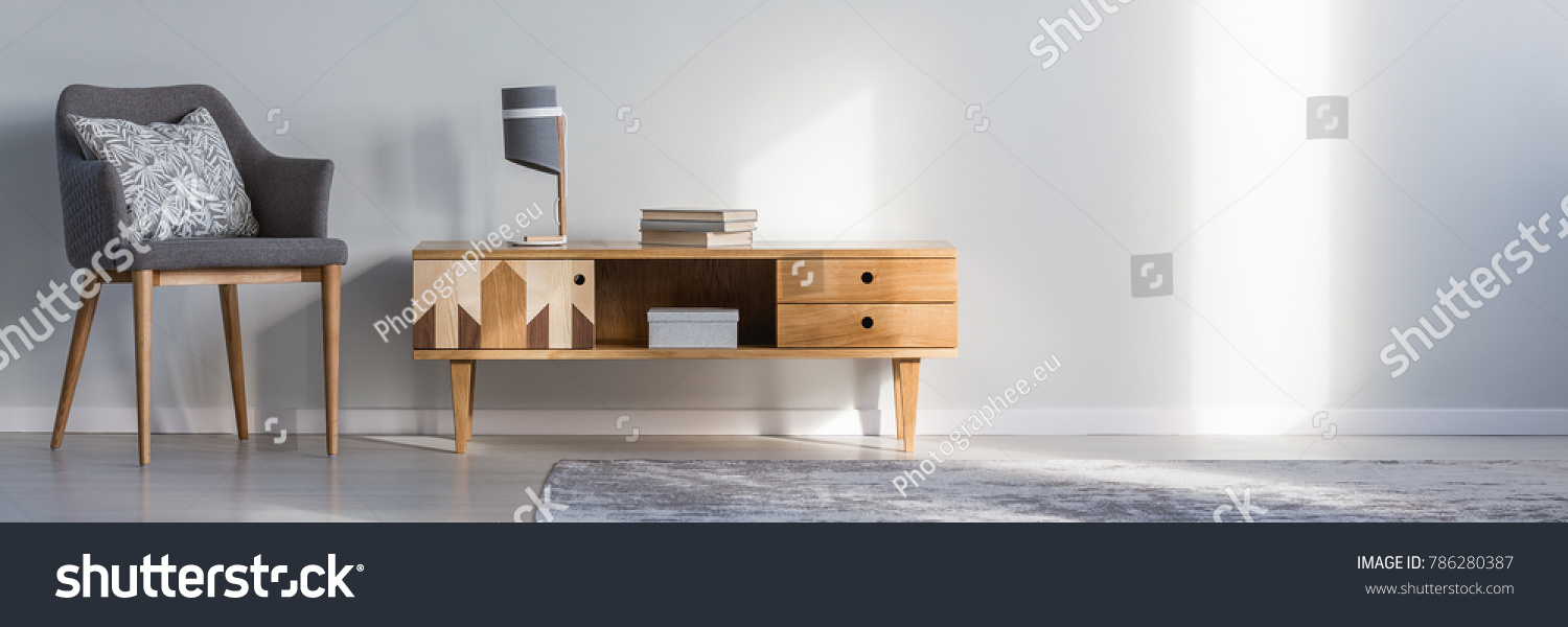 Books and lamp on rustic cupboard next to grey armchair with cushion against a wall with copy space in living room interior #786280387