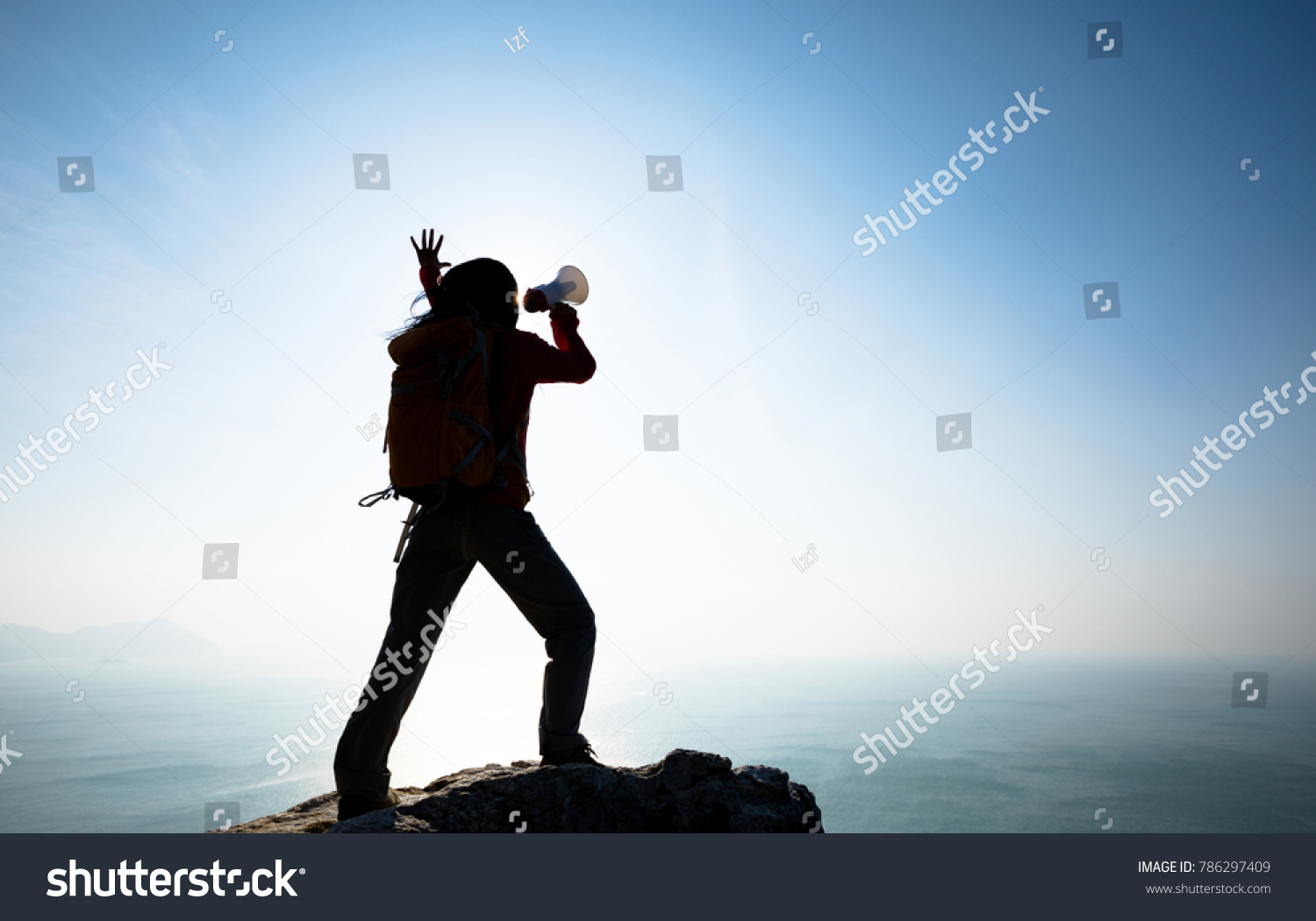 Young woman shouting with loudspeaker on windy sunrise coast cliff edge #786297409