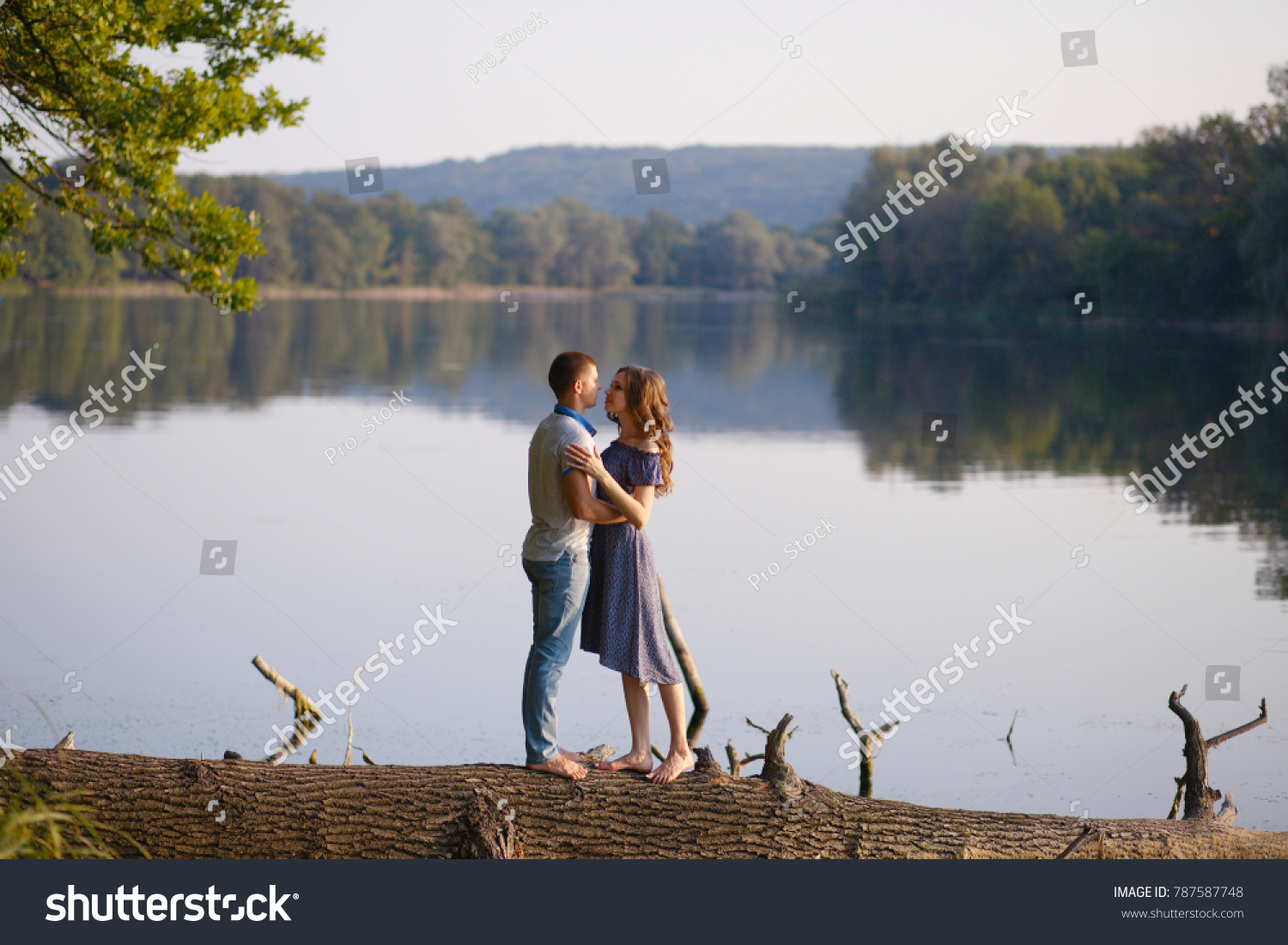 Romantic beautiful couple in love standing alone on a tree that lies in a lake with