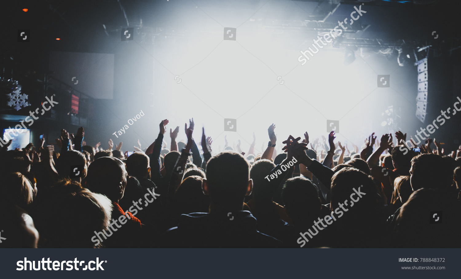 silhouettes of concert crowd in front of bright stage lights. Dark background, smoke, concert  spotlights #788848372
