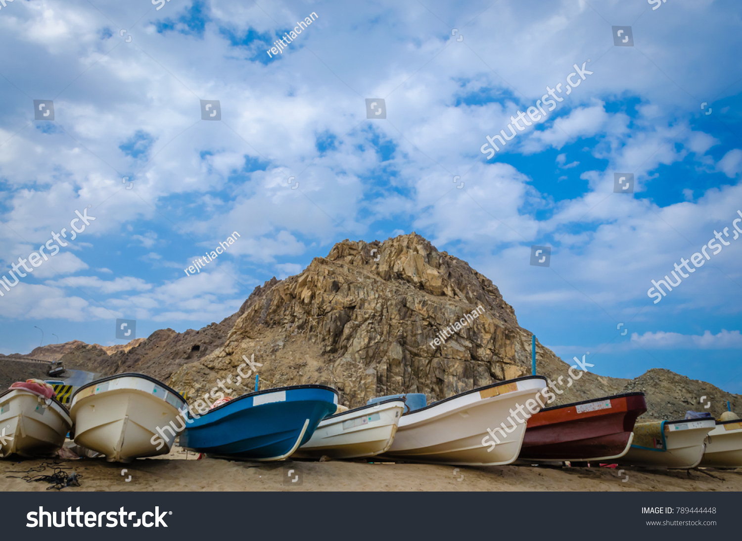 Fishing boats on the beach with a hill and a cloudy sky in the background.