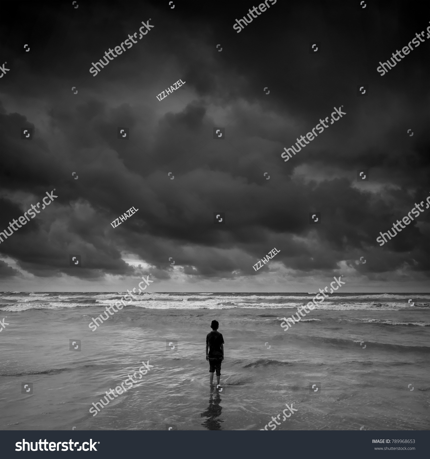 Lonely boy alone looking at the horizon near the beach during storm black and white photography