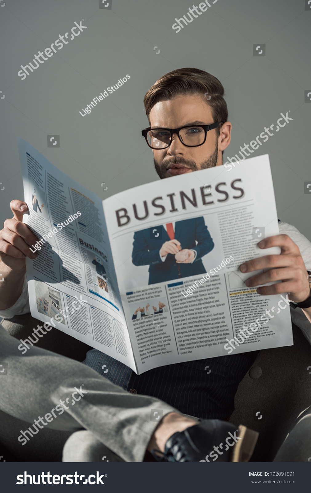 398fbfb68e portrait of stylish young businessman in eyeglasses reading newspaper  isolated on grey