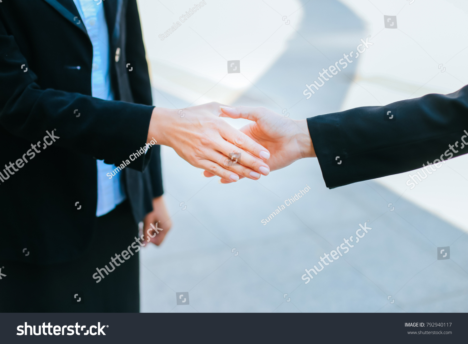 Close Up Of Two Business Women Shaking Hands While Standing Two