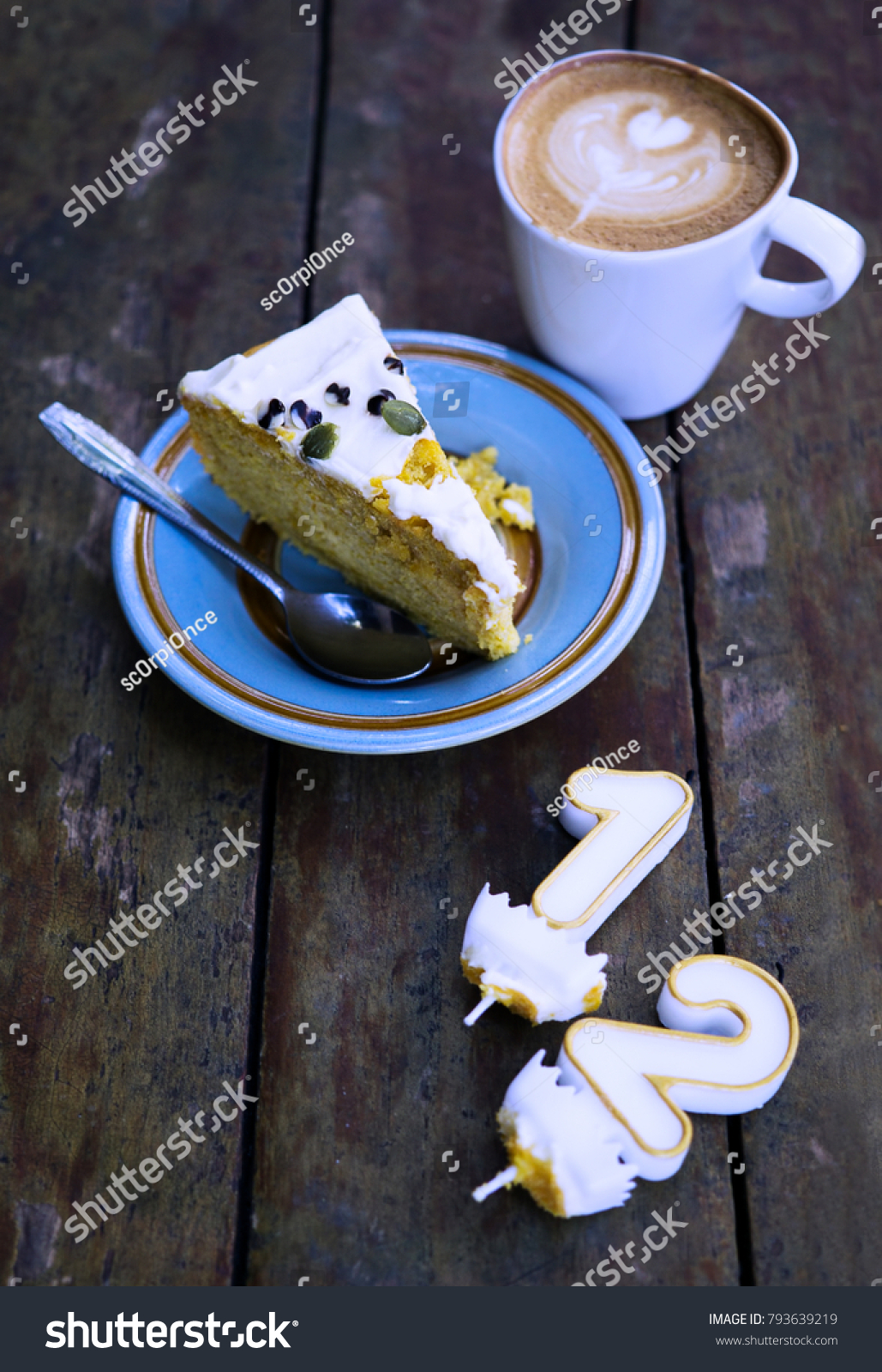 Slice Of Birthday Cake Witn Candle Numbers One And Two With Cup Latte On Wooden