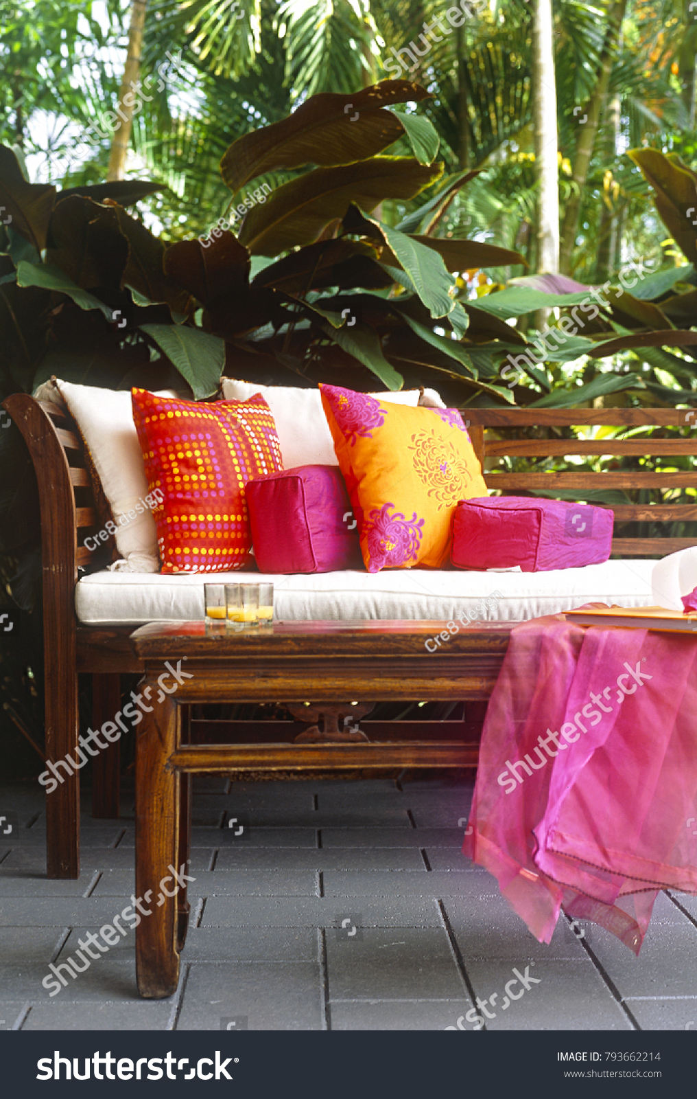 Balinese style teak outdoor furniture in courtyard with lush tropical garden behind