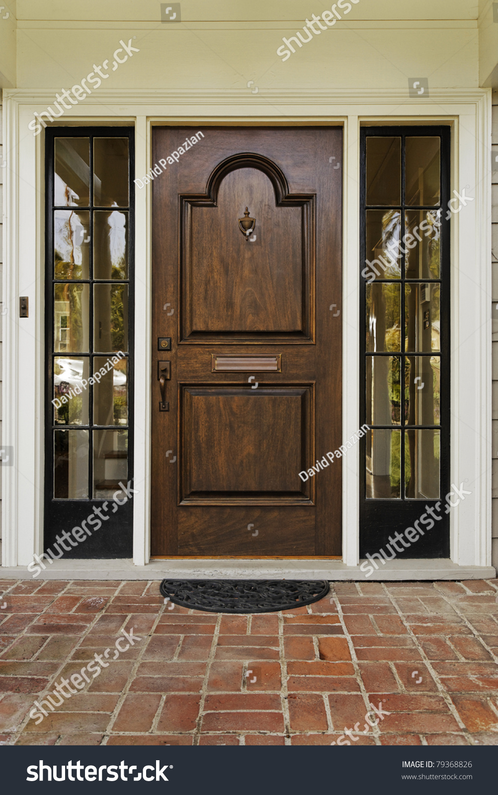 The Wooden Front Door Of A Home With Glass Panels To Each Side And Brick