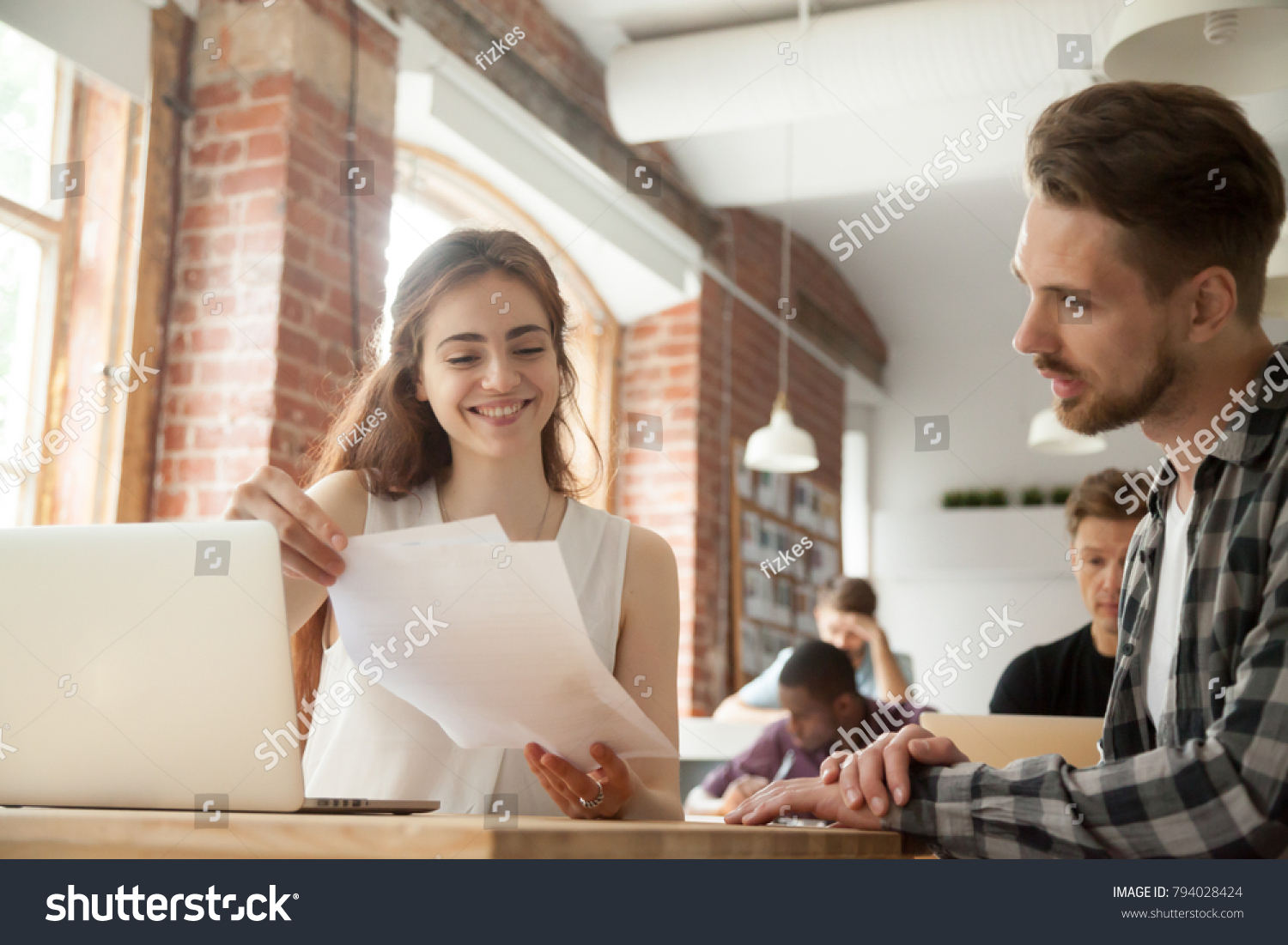 Businesswoman discussing business documents at meeting with client customer in shared office, smiling woman employee helping mentoring young man intern explaining corporate paperwork in co-working #794028424