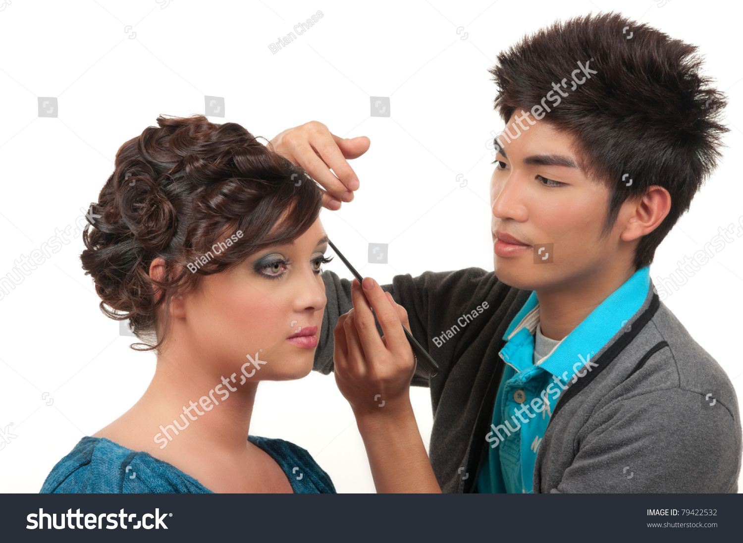 Cosmetics artist doing finishing touches of her customer's hair and make up before her prom,