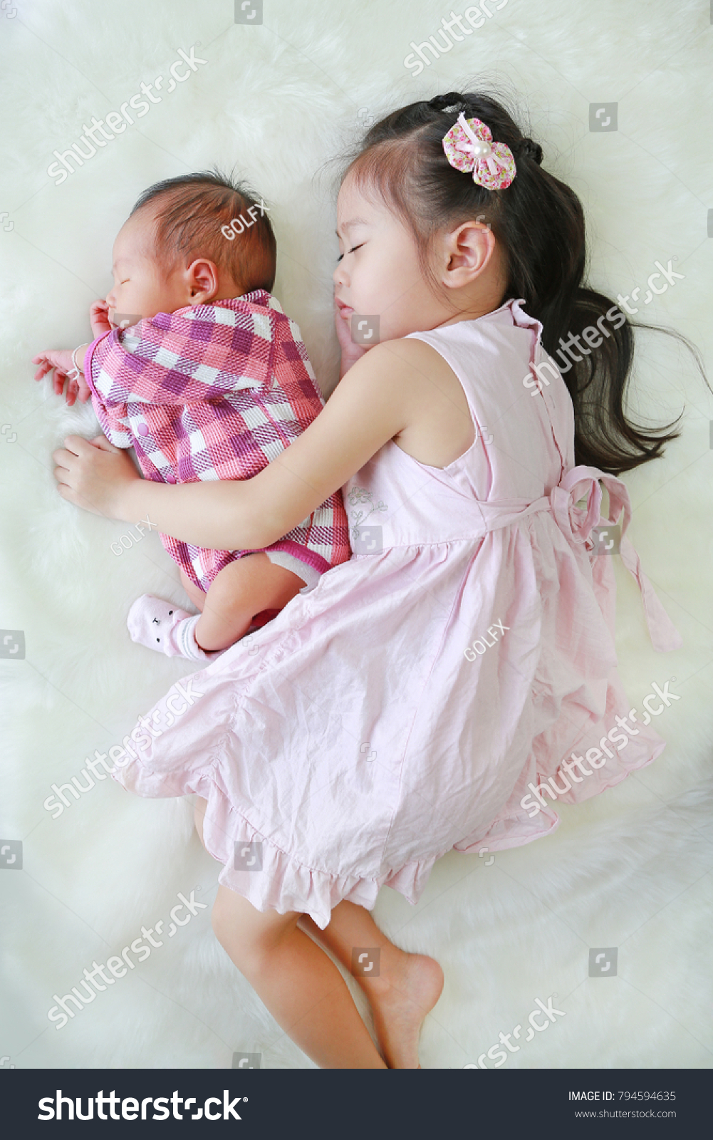 Cute Asian sister embracing sleeping newborn baby lying on white fur  background.