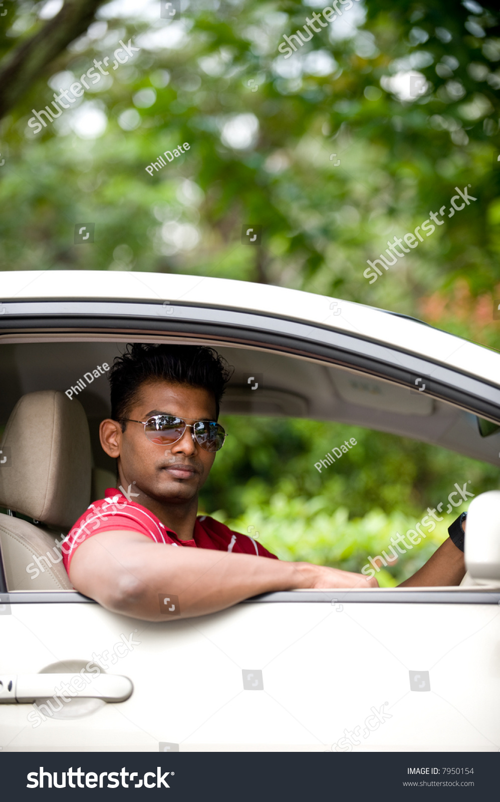 South Asian Indian young man sitting on drivers seat in