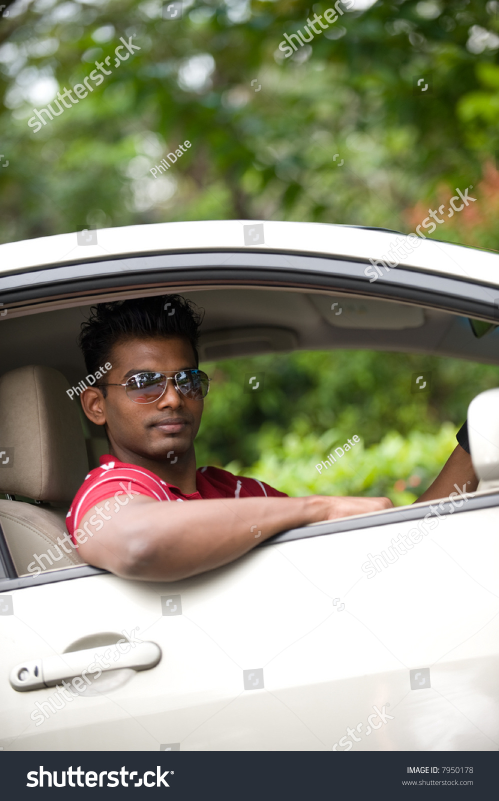A Good-Looking Indian Man In Sunglasses Sitting In Drivers