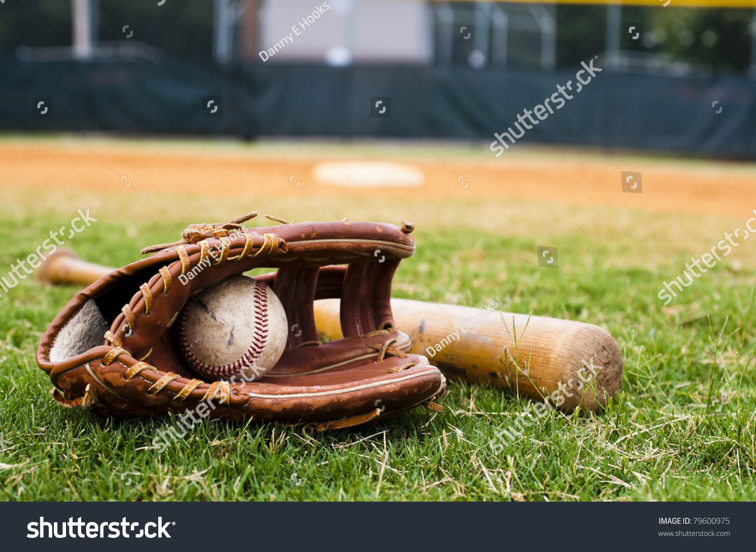Old baseball, glove, and bat on field with base and outfield in background. #79600975