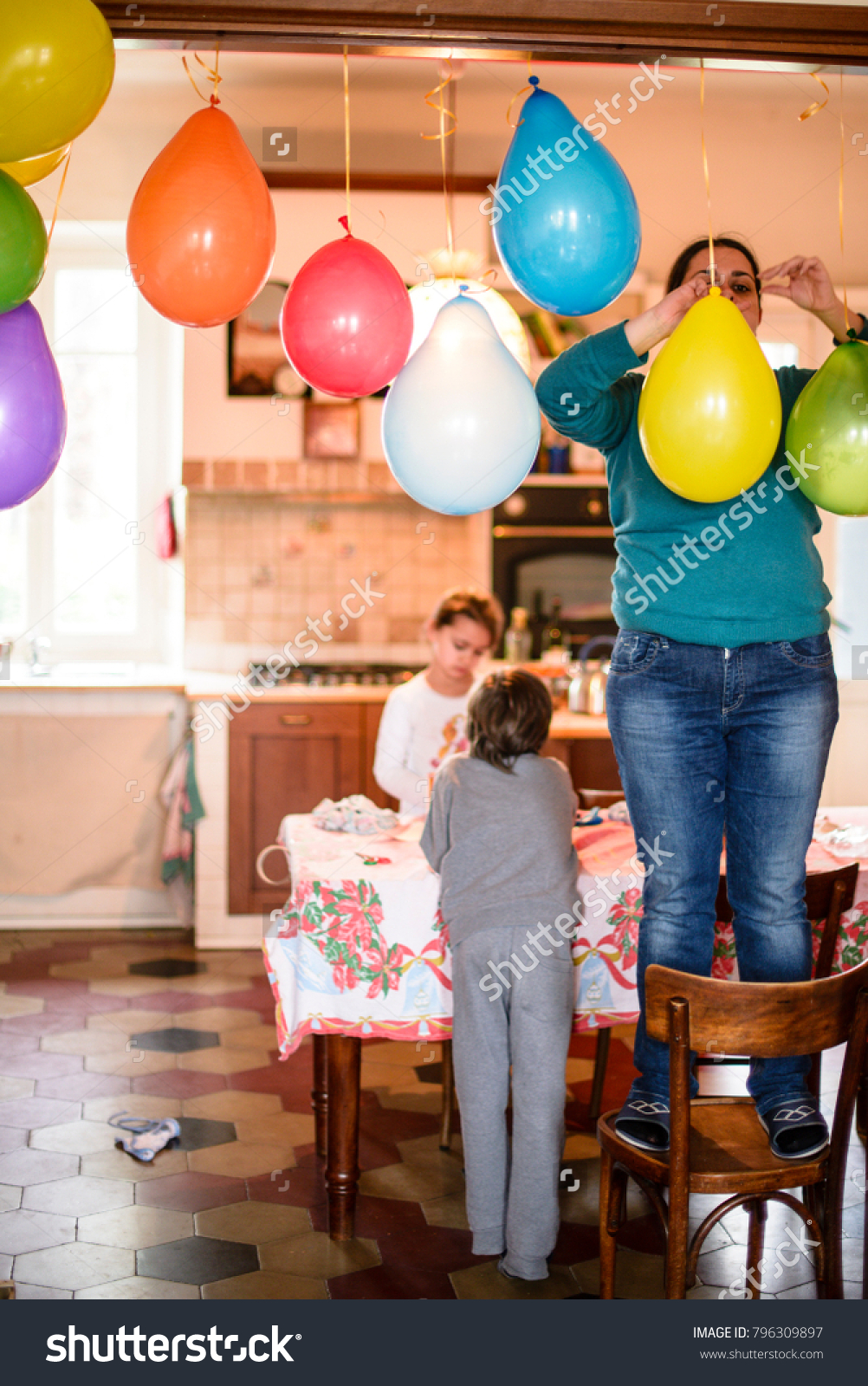 Mother With Children Hang Colorful Balloons For Birthday Party In Her Home Standing On