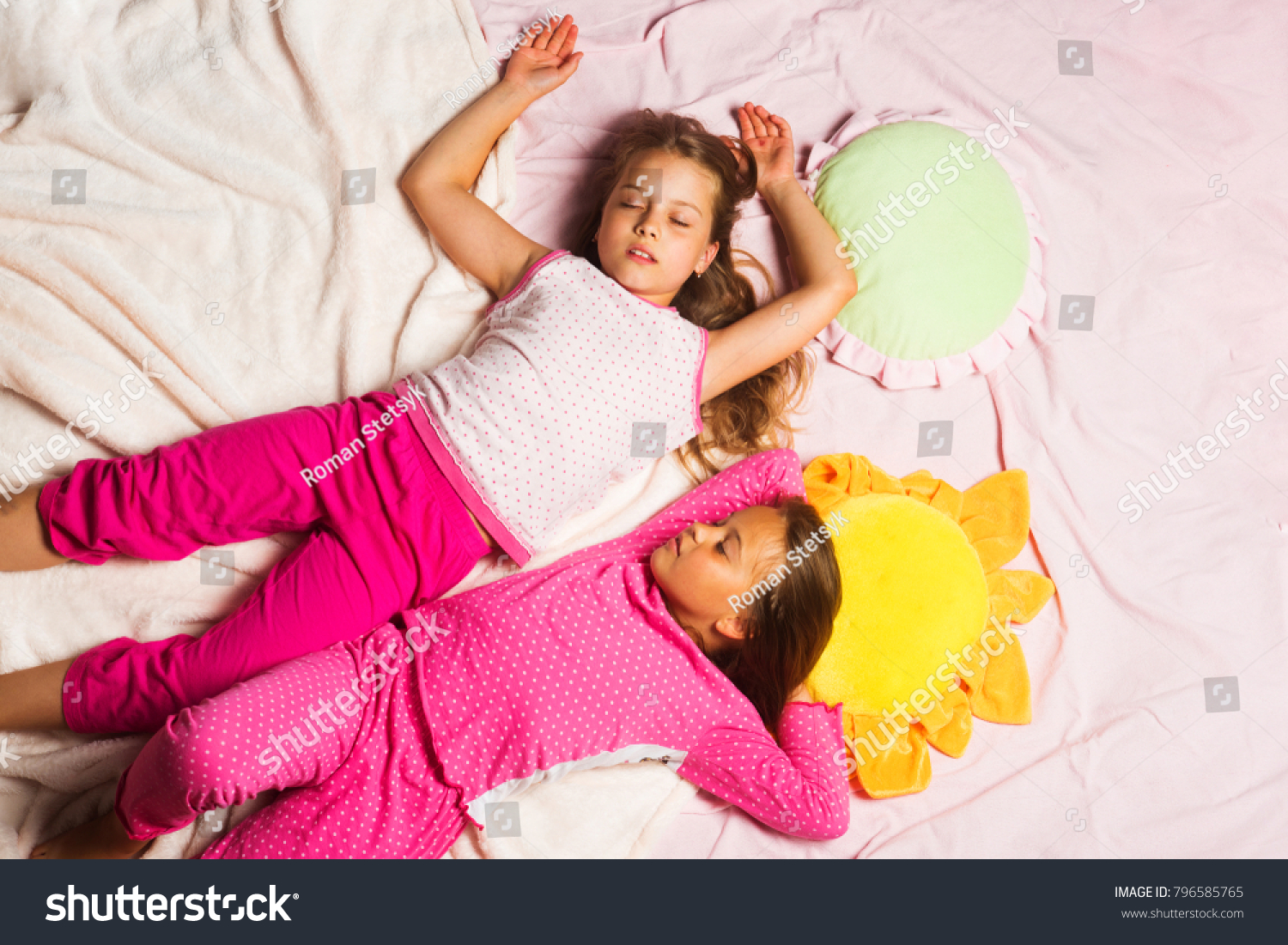 71895055c6 Children with sleepy faces lie close on light pink blanket background.  Schoolgirls having pajama party