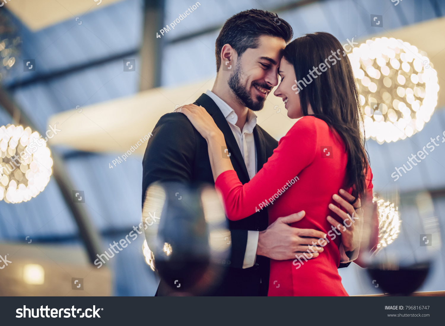 Beautiful loving couple is spending time together in modern restaurant. Attractive young woman in dress and handsome man in suit are having romantic dinner. Celebrating Saint Valentine's Day. #796816747