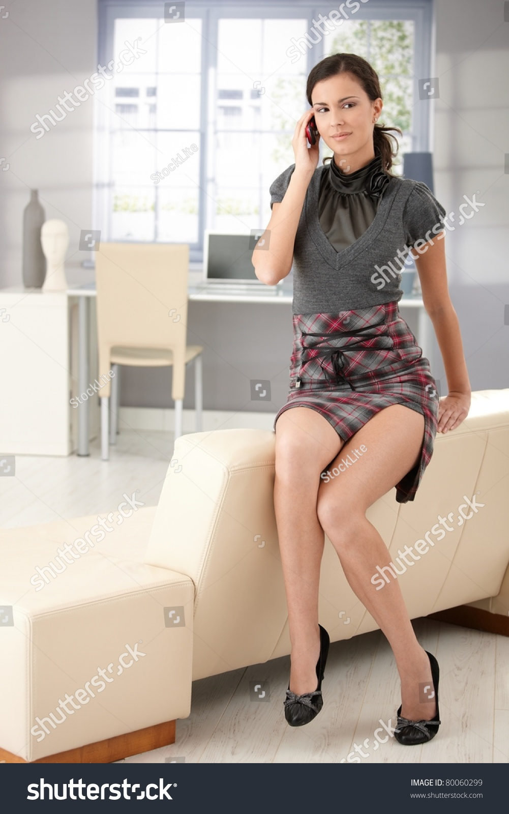 bbbaa123b Sexy young woman sitting on sofa, chatting on mobile, wearing mini skirt.?