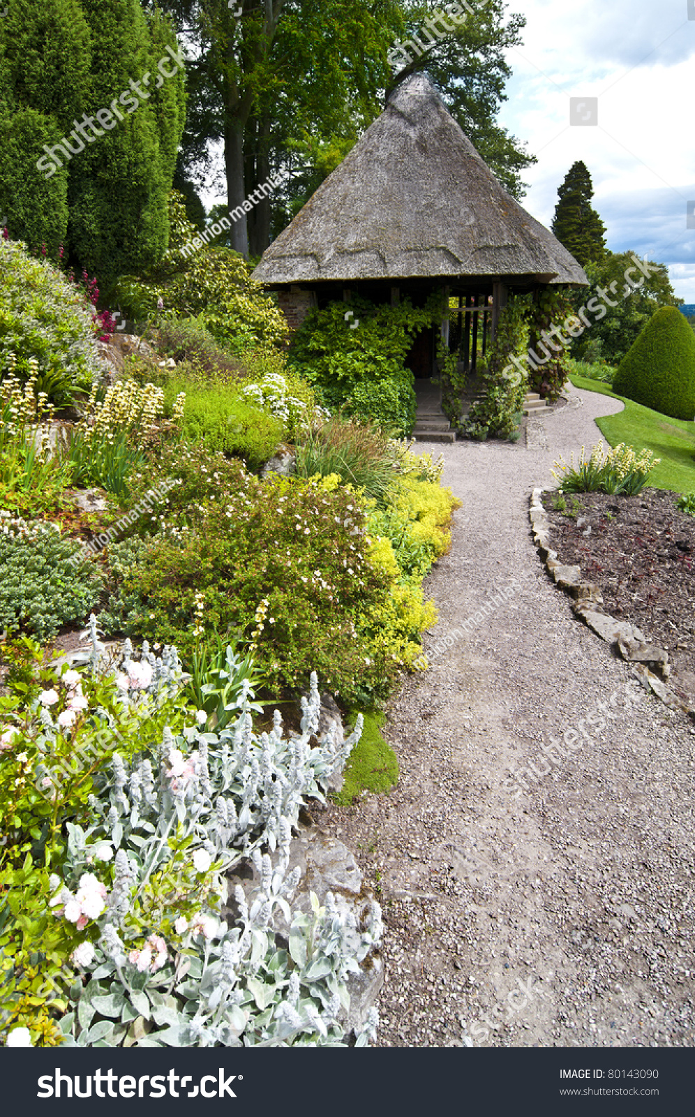 A gravel path leads through beautiful flower beds to a for Beautiful flower beds