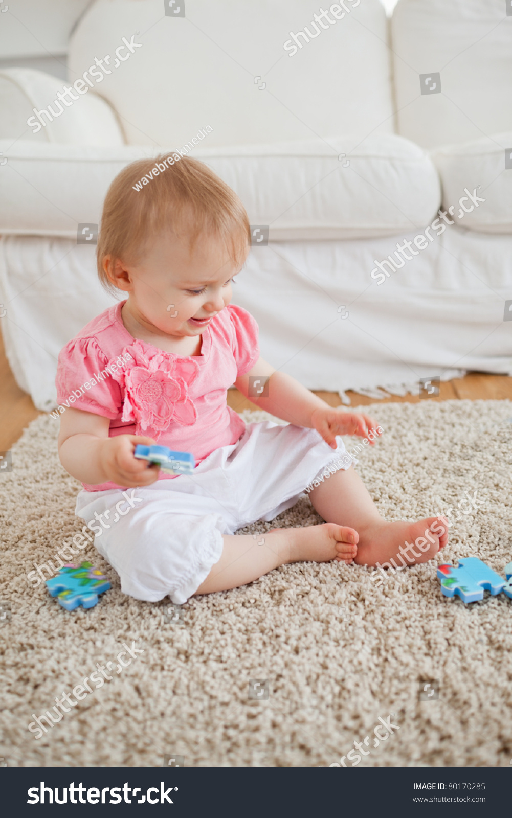 Baby Playing With Puzzle Pieces While Sitting On A Carpet In The Living Room Stock Photo