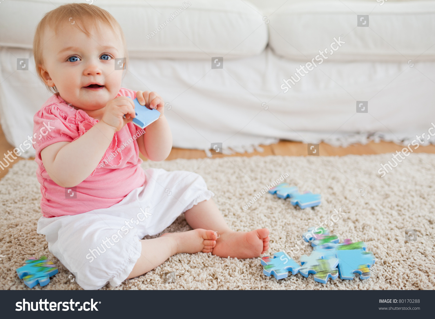 Cute Blond Baby Playing With Puzzle Pieces While Sitting On A Carpet In The Living Room Stock