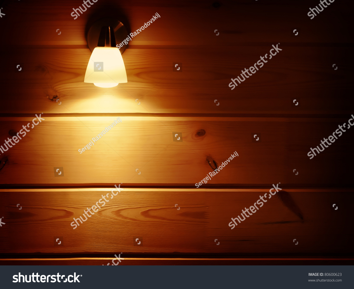 Switched On Lamp Bracket At The Wooden Wall Stock Photo