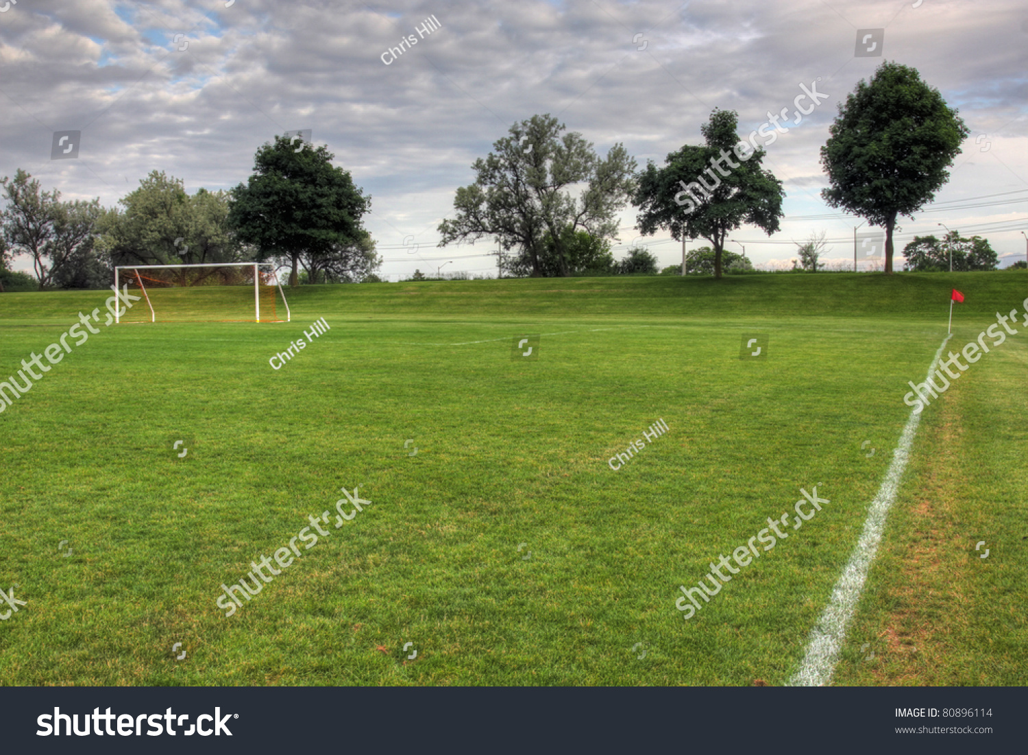 Cloudy unoccupied soccer field trees background stock photo a cloudy unoccupied soccer field with trees in the background hdr photograph altavistaventures Gallery