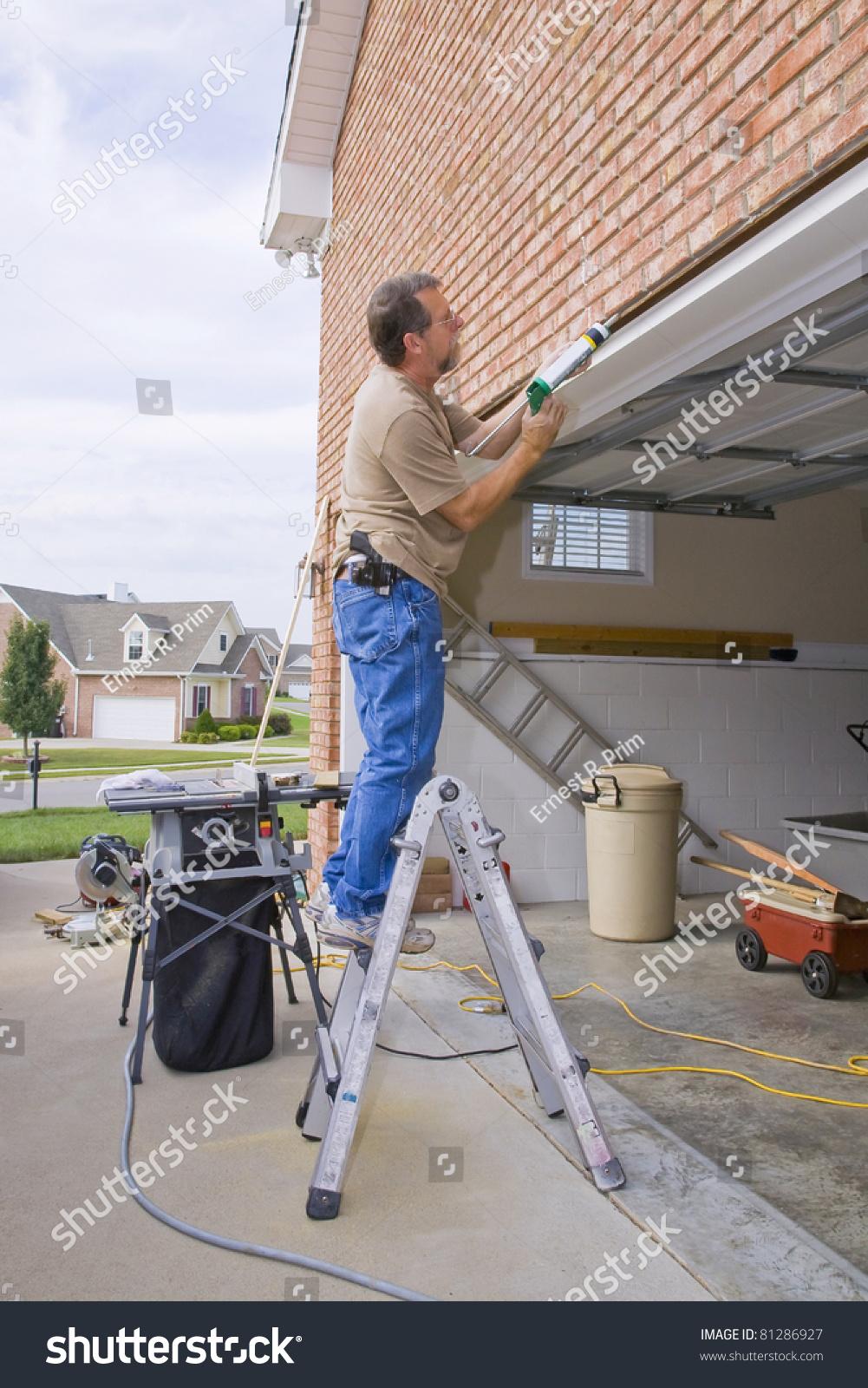 Carpenter caulking cracks between garage door stock photo for Garage door repair st petersburg