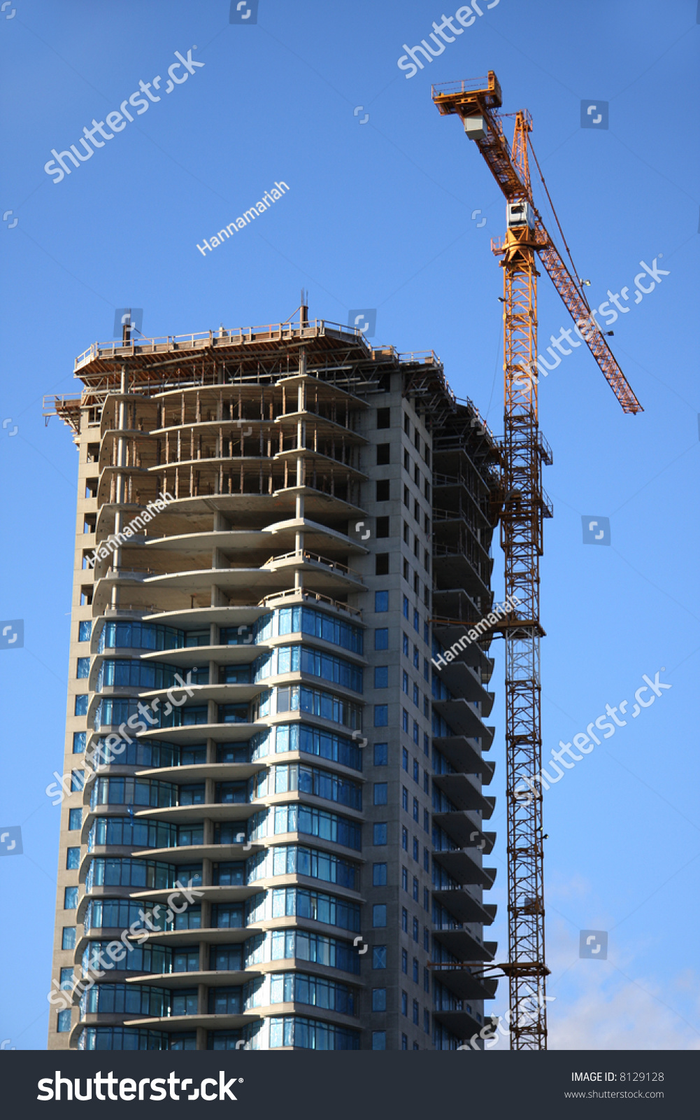 high rise construction site with crane against a bright