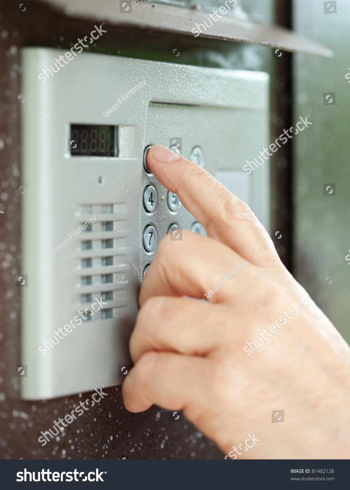 Close Up Of Person Using Building Intercom Stock Photo