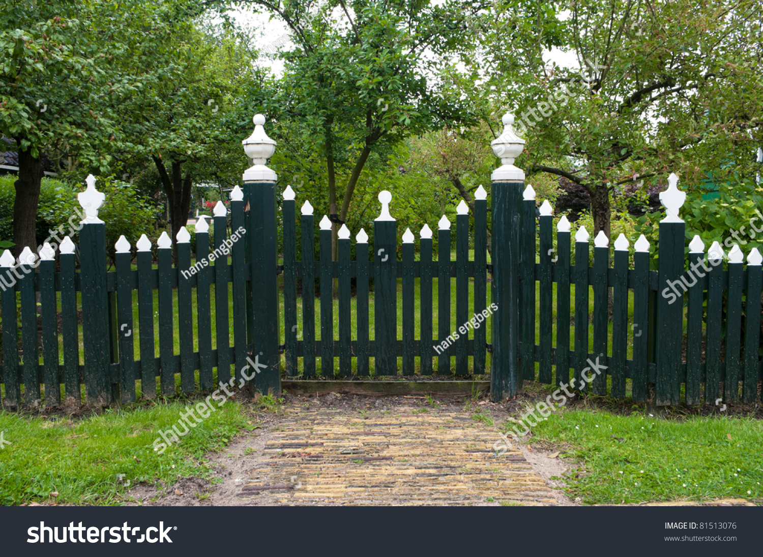 Green Wooden Picket Fence With White Tops Stock Photo