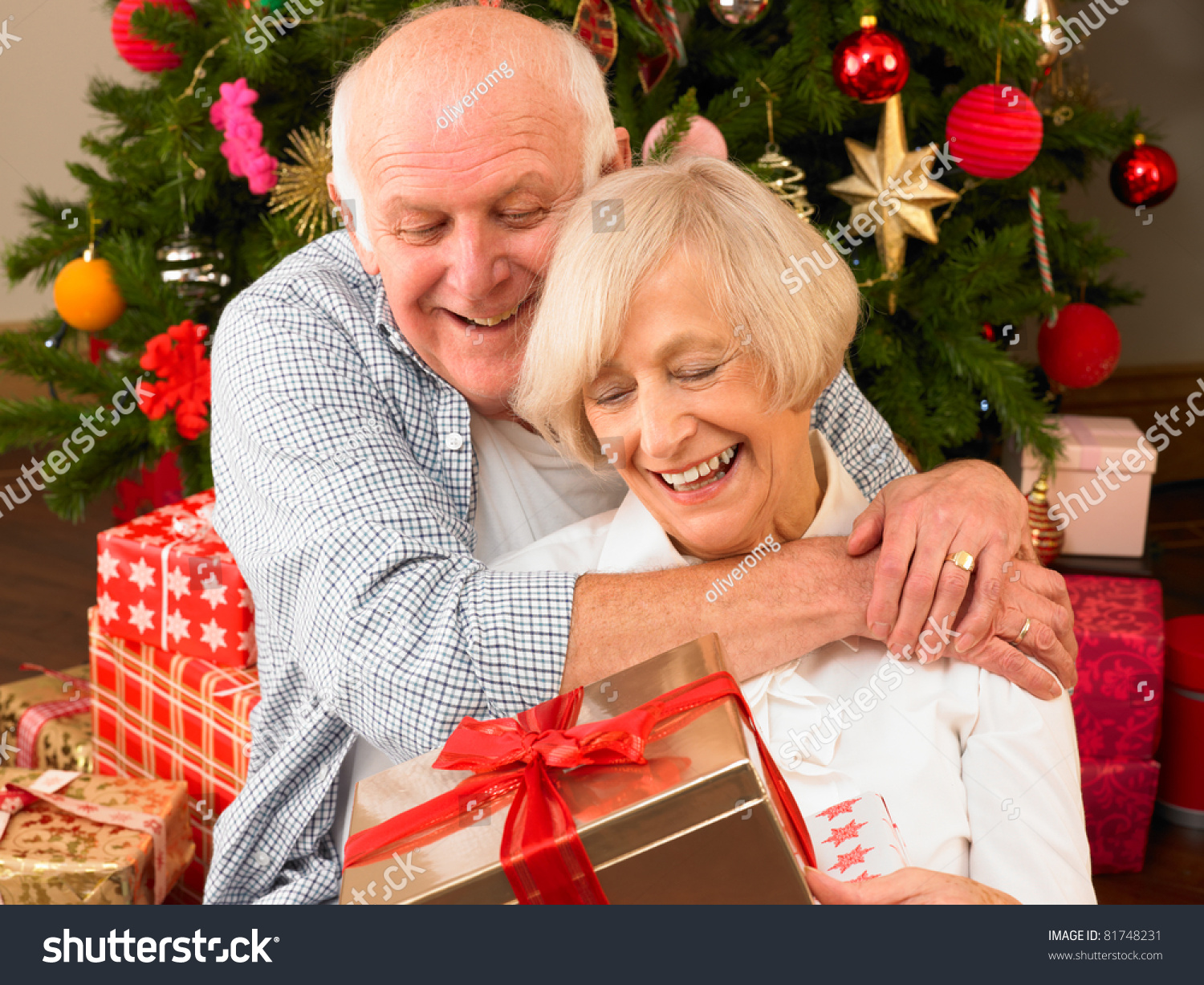 Senior Christmas Gifts: Senior Couple With Gifts In Front Of Christmas Tree Stock
