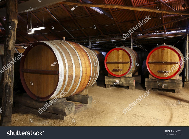 stacked oak barrels maturing red wine. oak wine barrels in a winery cellar stacked maturing red