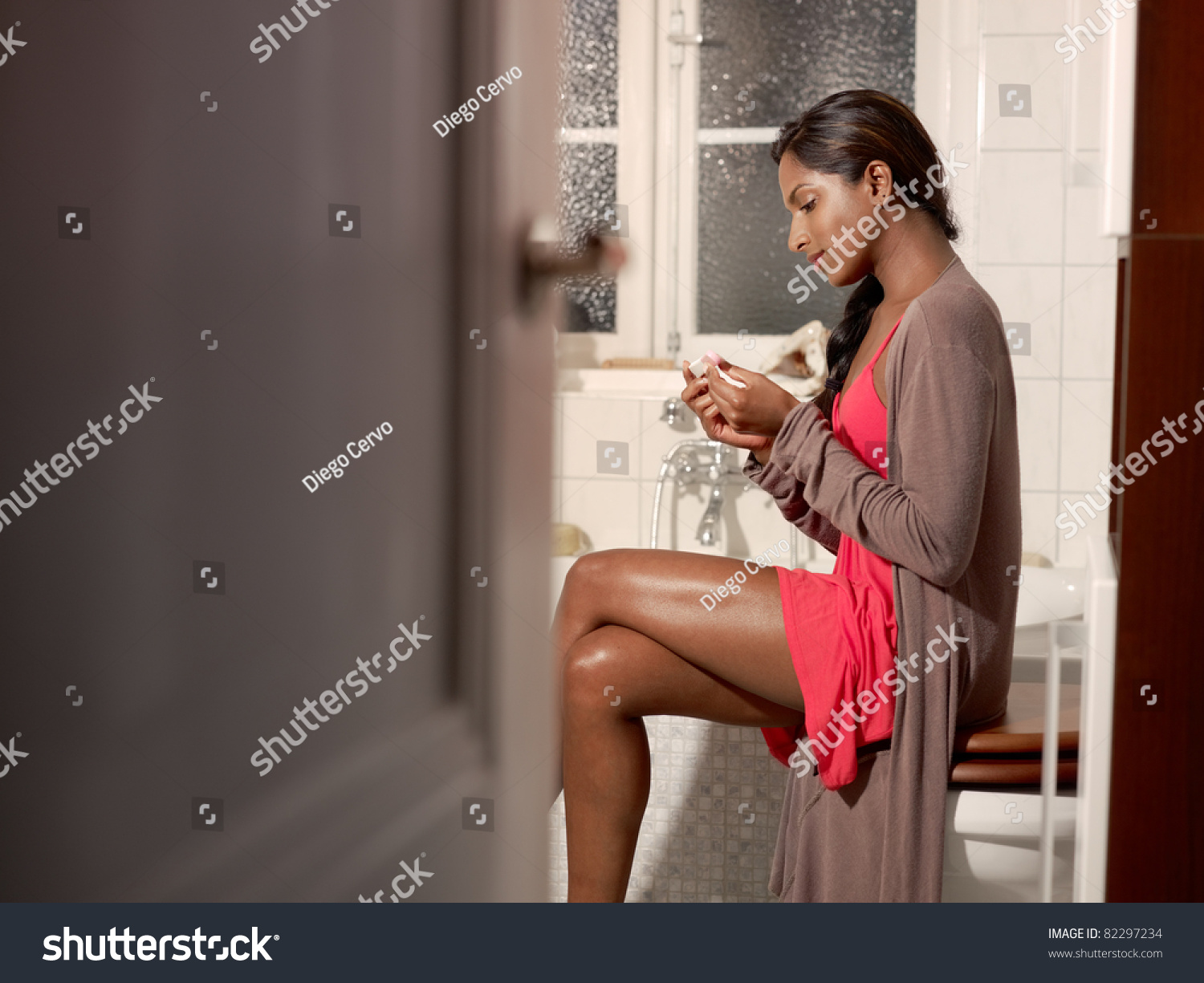 Happy Young Woman Using Pregnancy Test In Bathroom Horizontal. Black And White Tile Floor Bathroom
