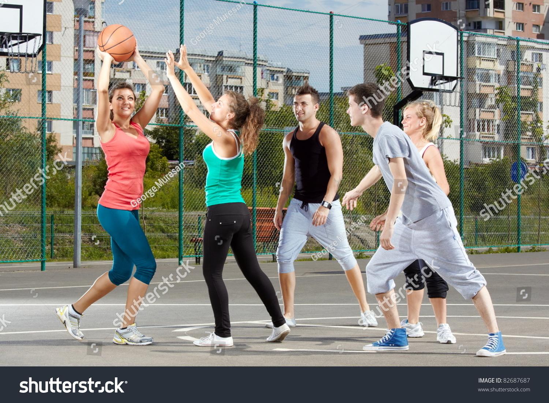 A Woman Playing Basketball Imágenes De Stock A Woman: Young Men And Women Playing Basketball In A Park Stock