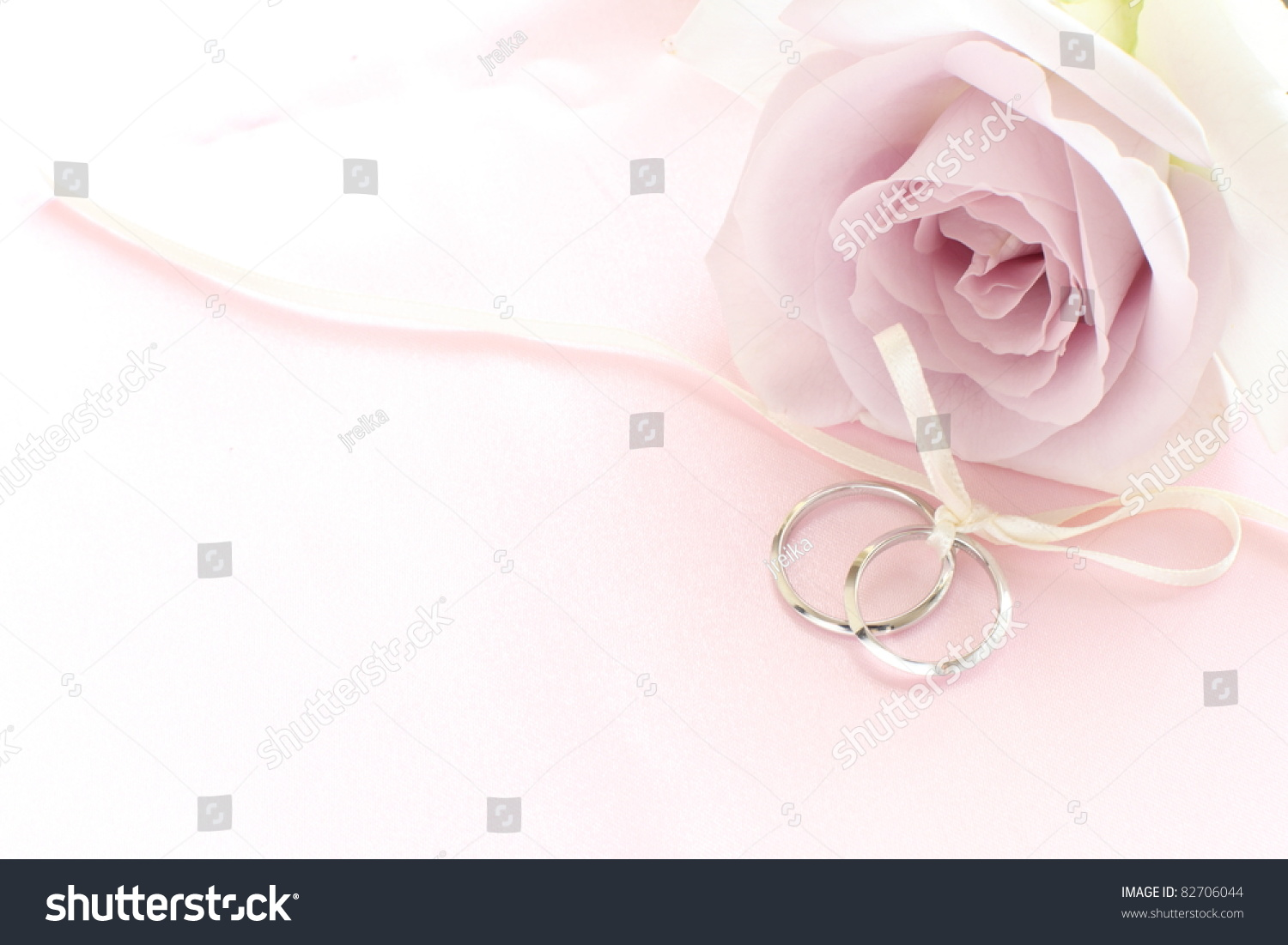 pair of wedding rings with pastel purple rose for